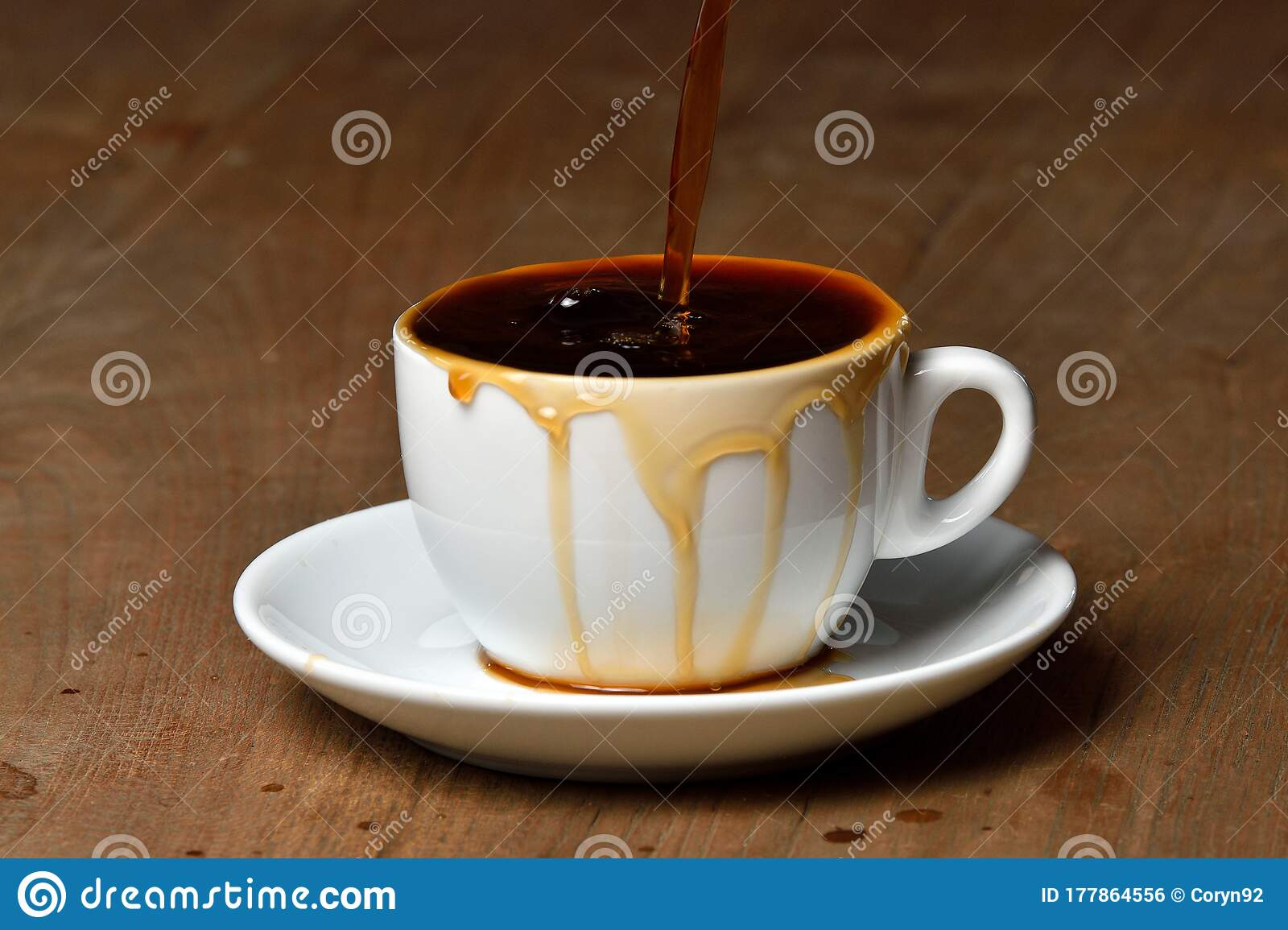 Pouring Coffee Into Overflowed White Porcelain Mug With Saucer Cup With Overflowing Coffee Full Cup Of Coffee On Wooden Table Stock Photo Image Of Cafeteria Food 177864556
