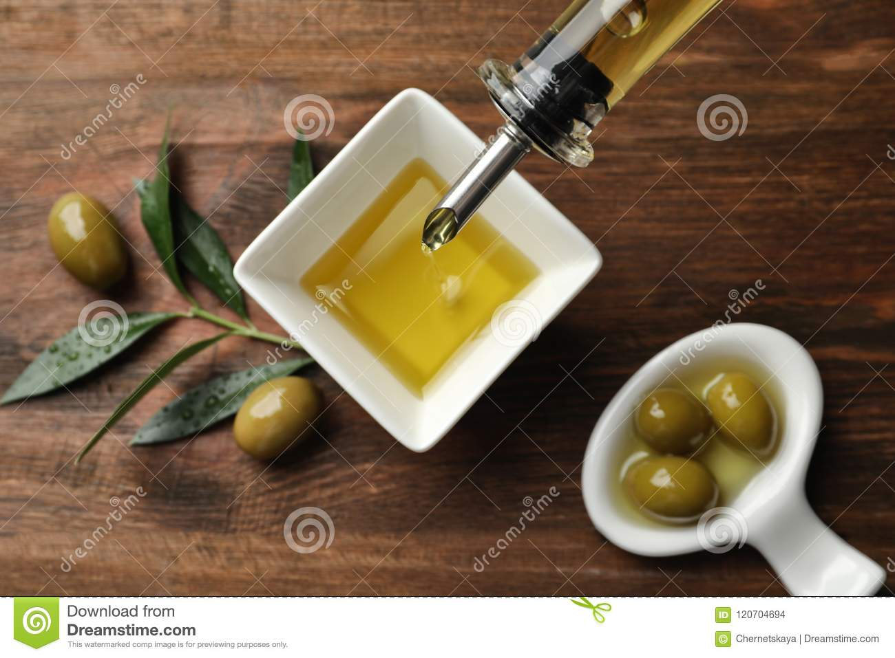 Pouring fresh olive oil into bowl on table,