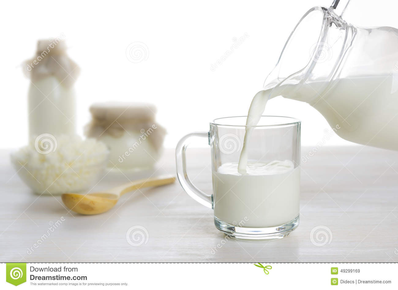 Pouring milk into the glass on dairy products background