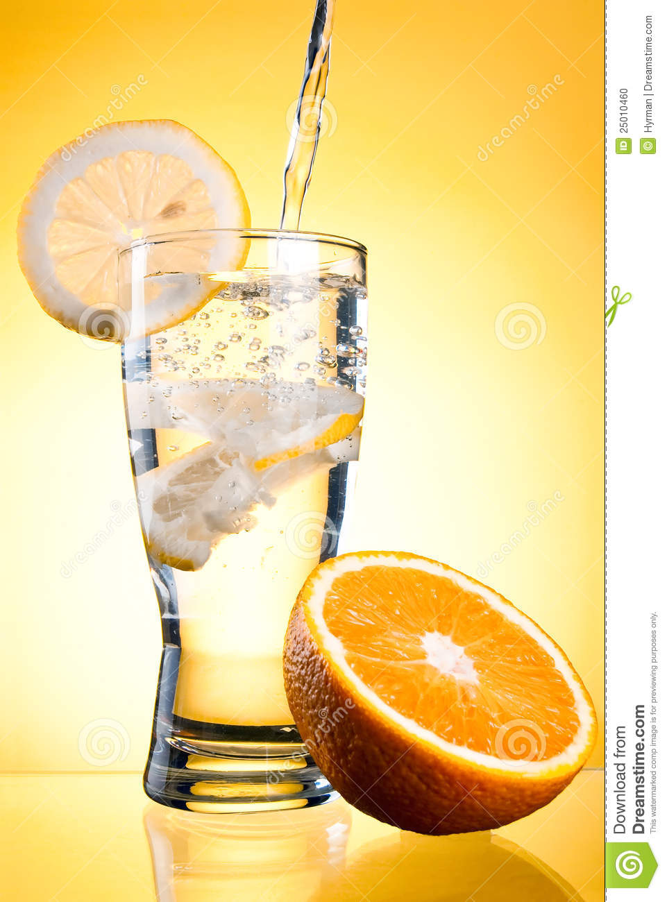 Pouring of mineral water in glass with lemon