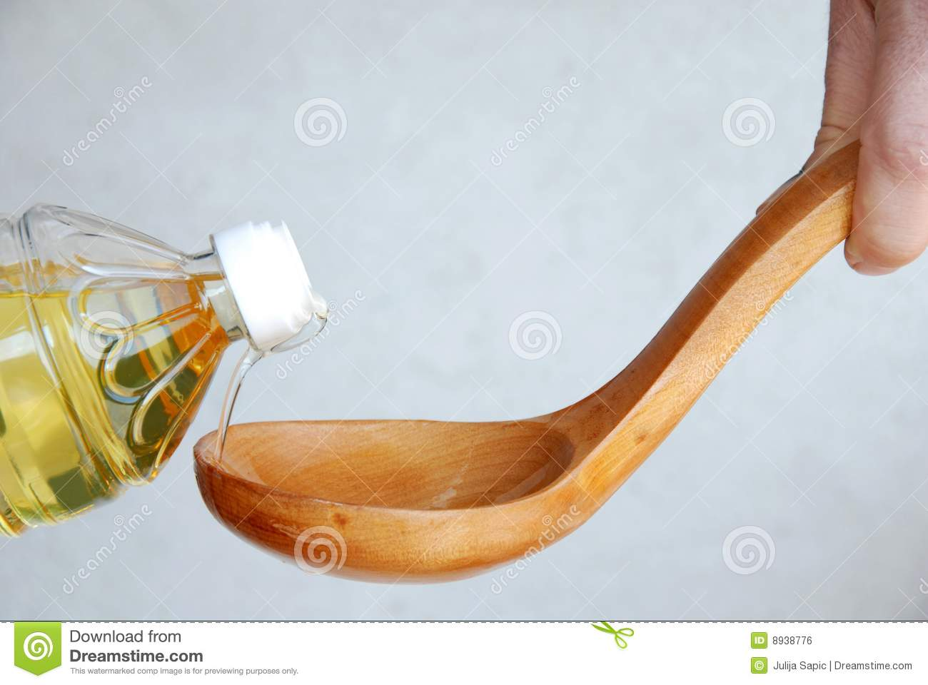 Pouring oil in wooden spoon