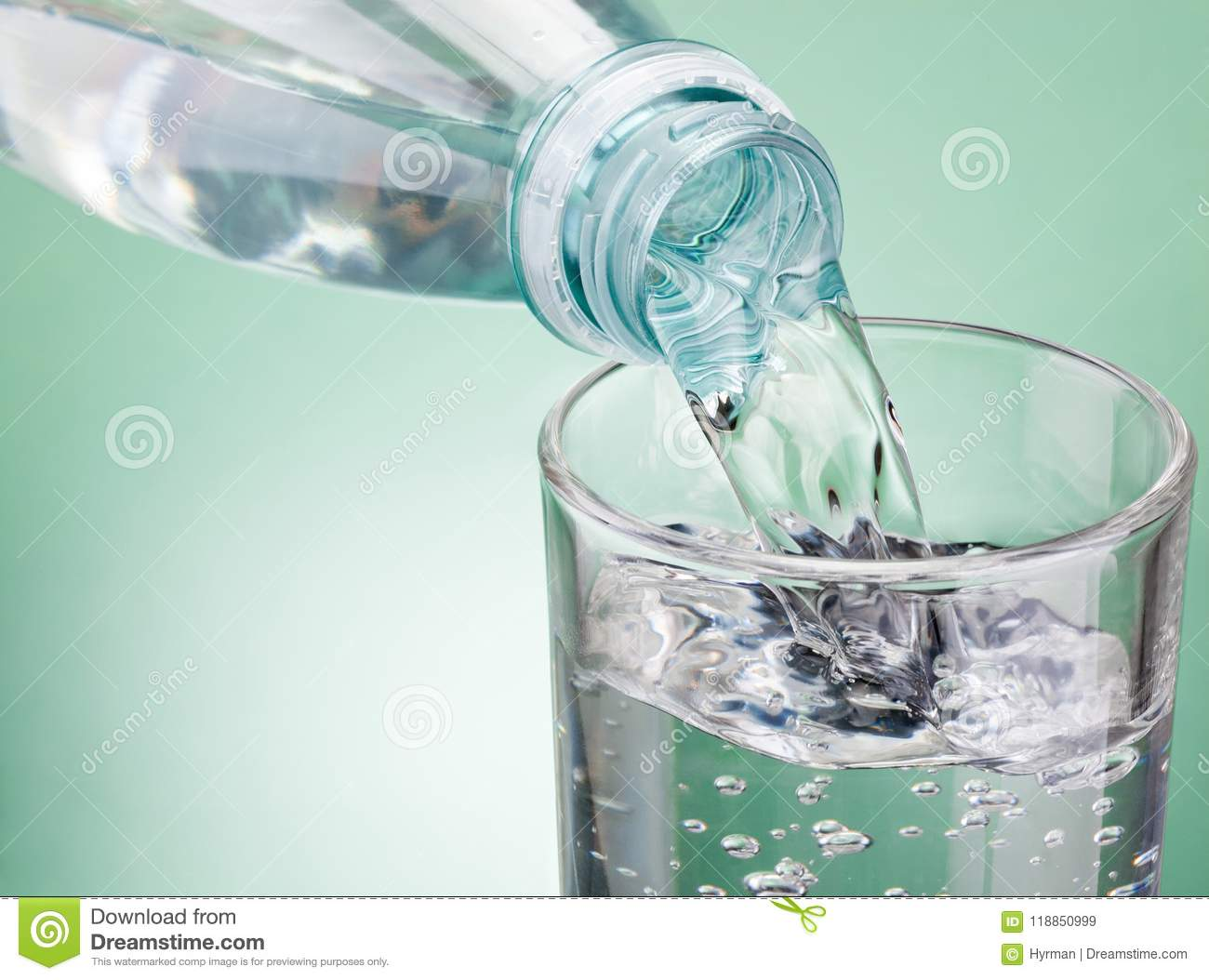 Pouring water from bottle into glass on green background