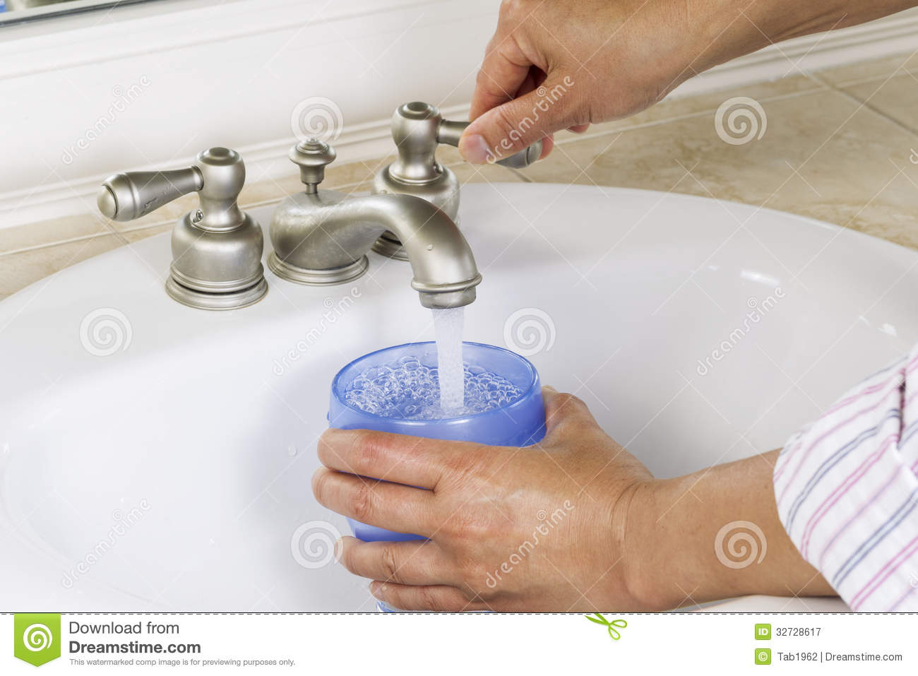 Pouring Water Into Cup From Bathroom Sink Royalty Free