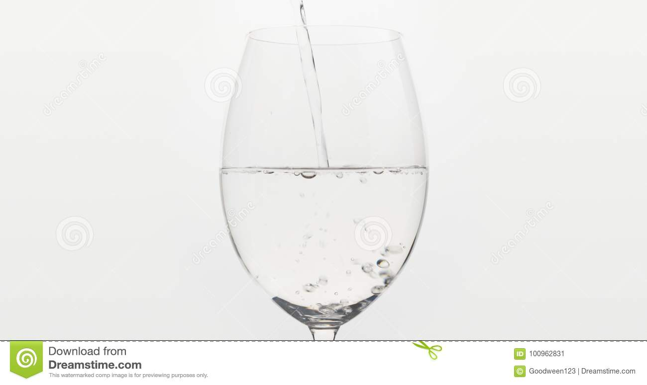 Pouring Water Into Wine Glass Over White Background Stock