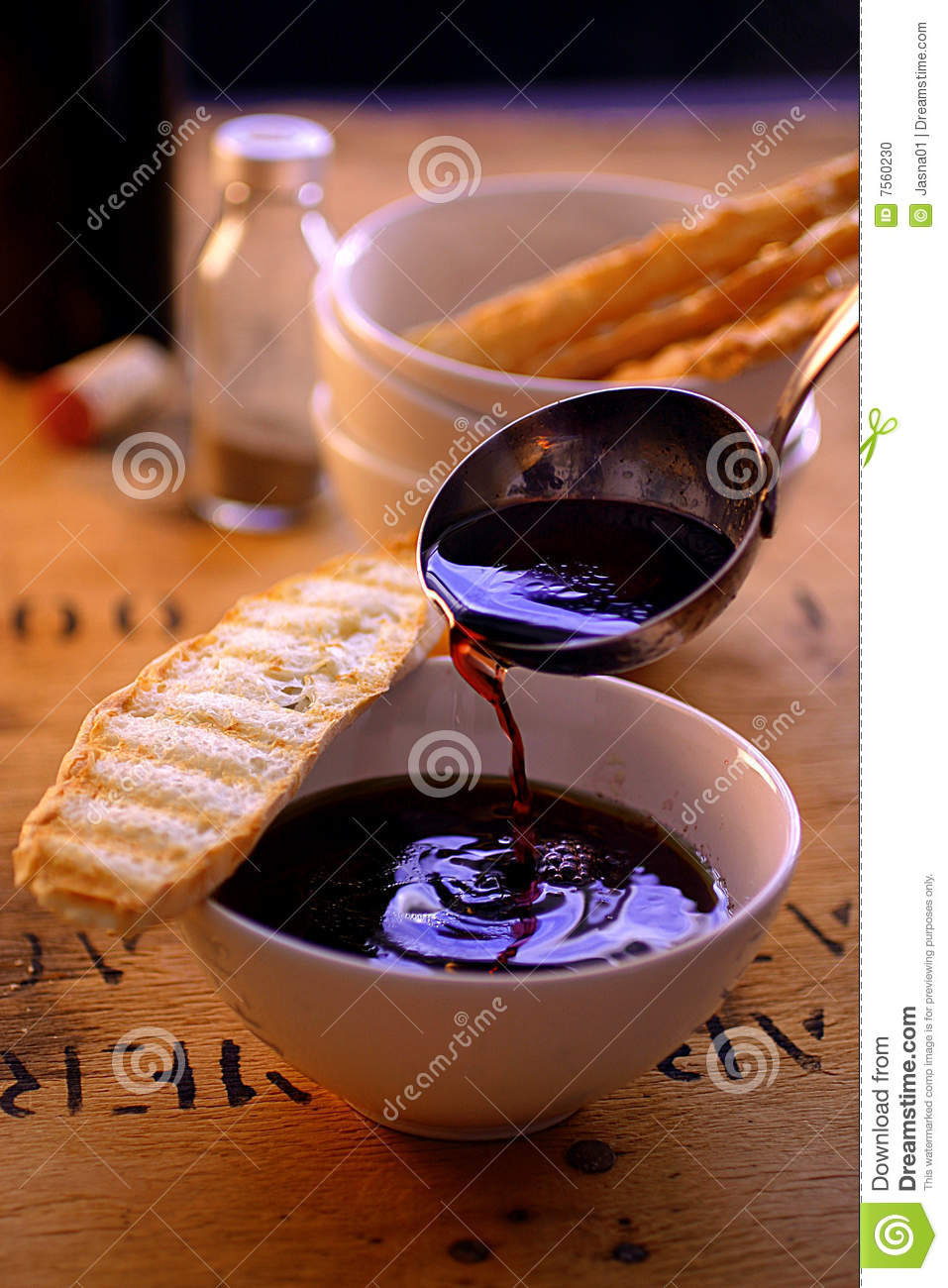 Pouring wine soup with toasted bread