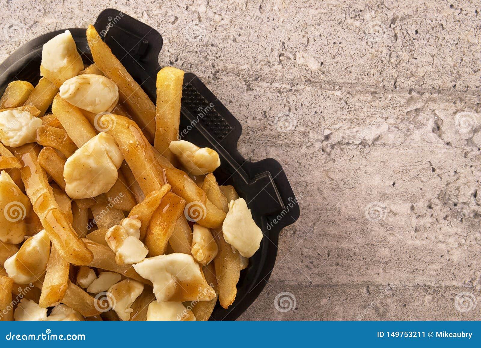 Poutine em um recipiente para viagem Cozinhado com queijo das batatas fritas, do molho e de coalho