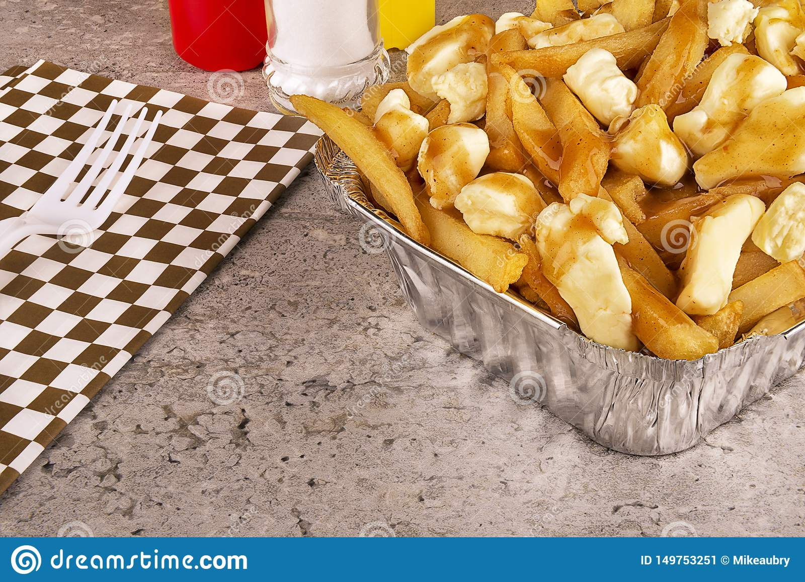 Poutine i en f?r avh?mtning beh?llare Lagat mat med fransk sm?fisk-, sky- och ostmassaost