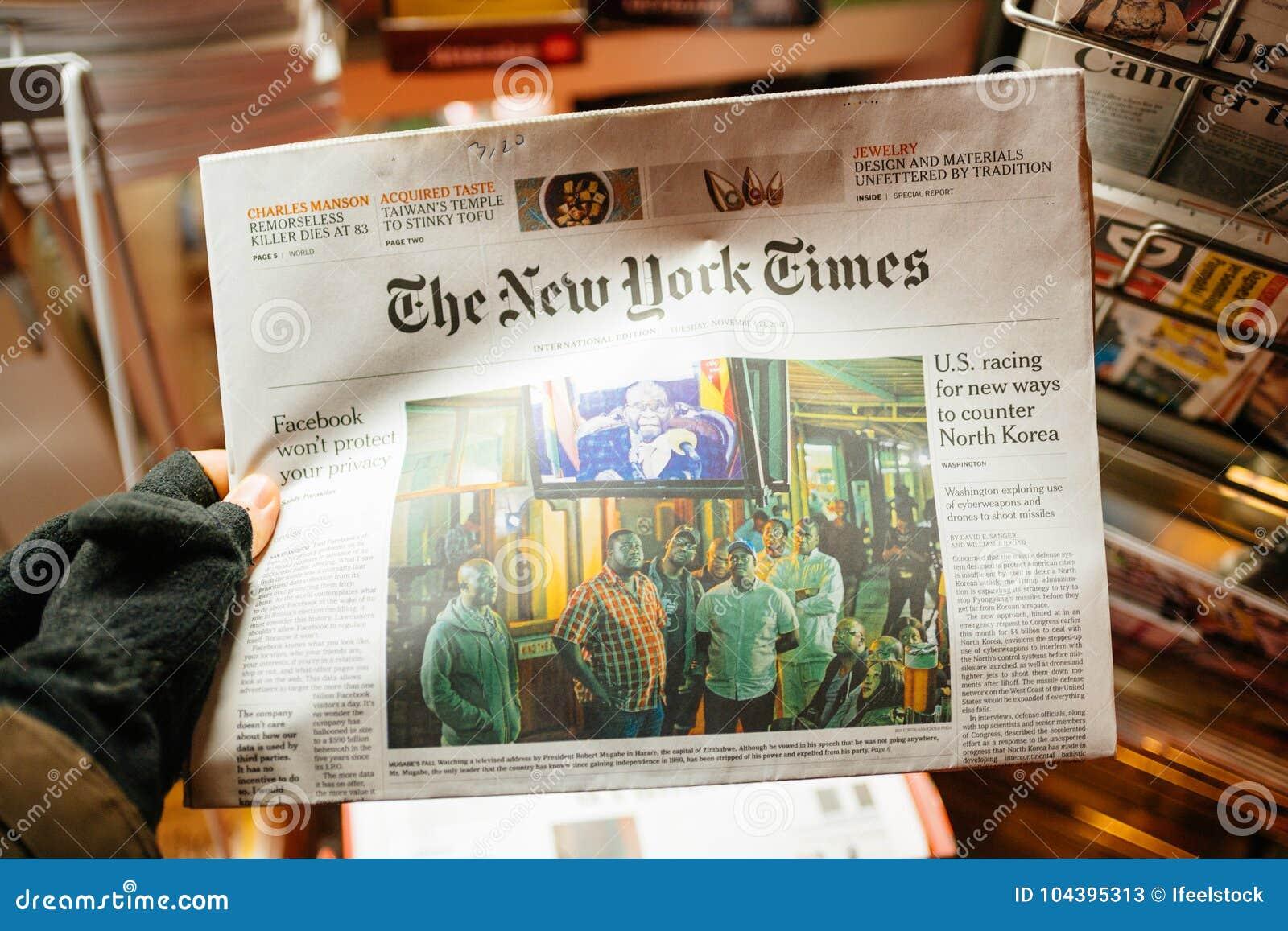 POV das luvas vestindo da mão masculina que guardam New York Times Mugab