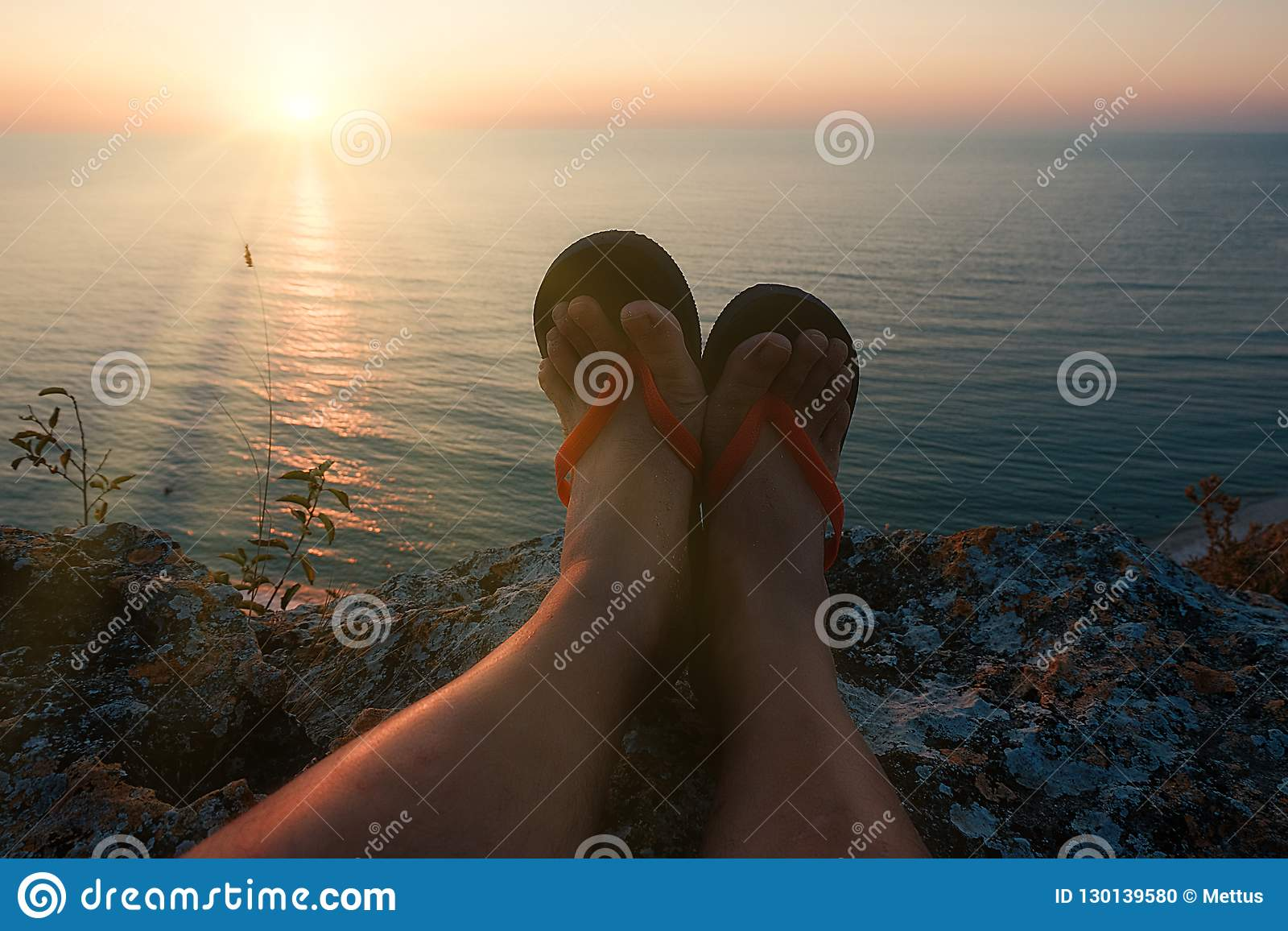 POV view of mans legs in flip-flops on the high cliff in front of setting sun