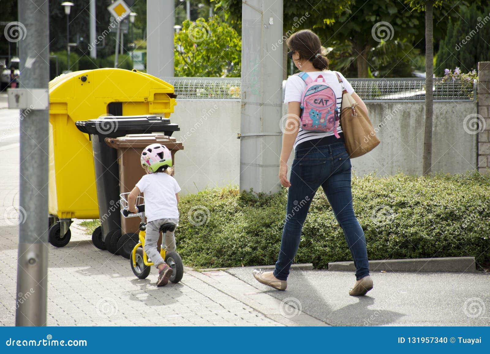 Povos alemães da mãe que olham a prática da menina das crianças que dá um ciclo no passeio ao lado da estrada em Heidelberg, Alem