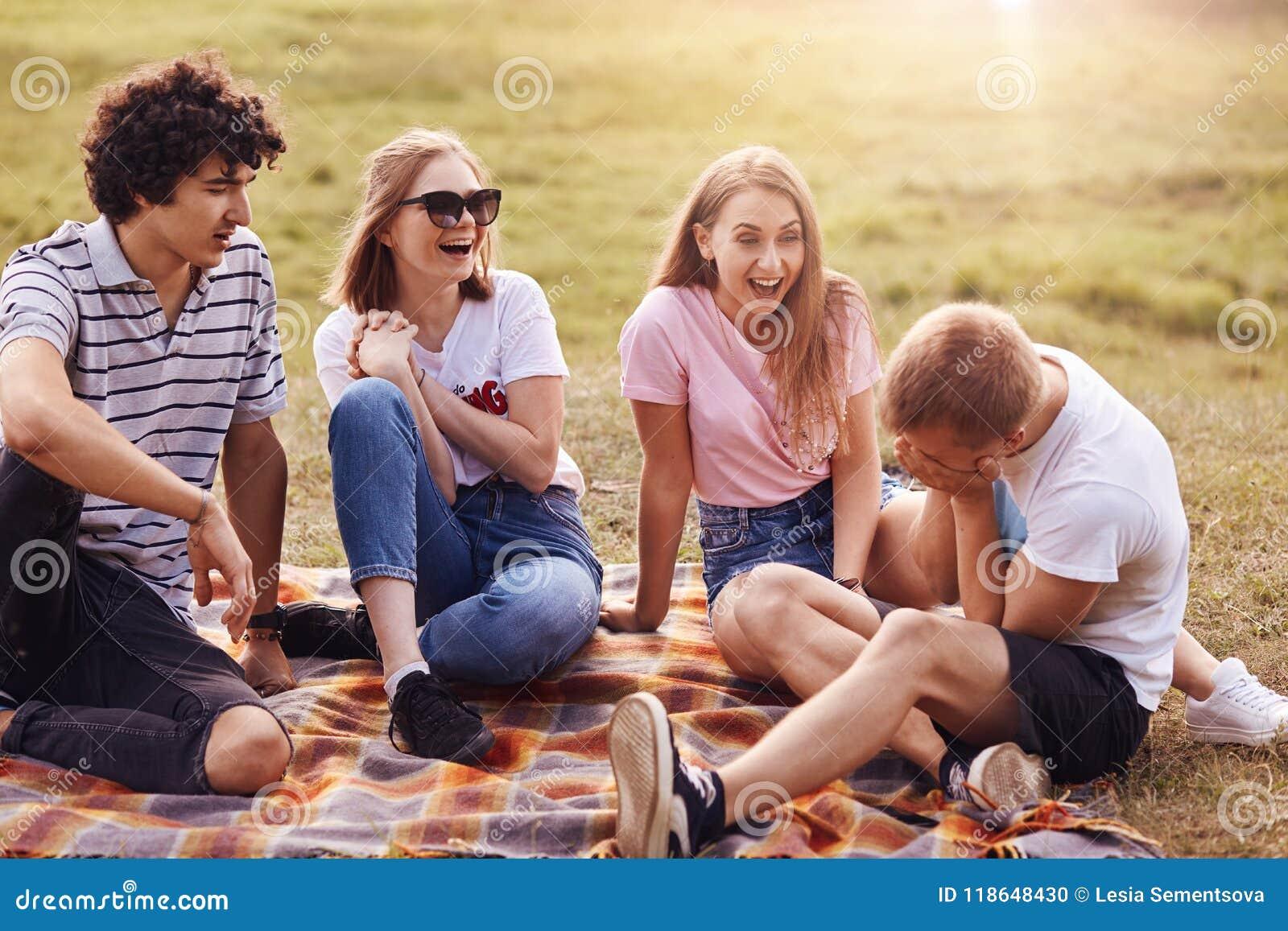 Povos, amizade e divertimento Quatro homens e amigos das mulheres passam o fim de semana exterior, riem de estórias boas, têm exp