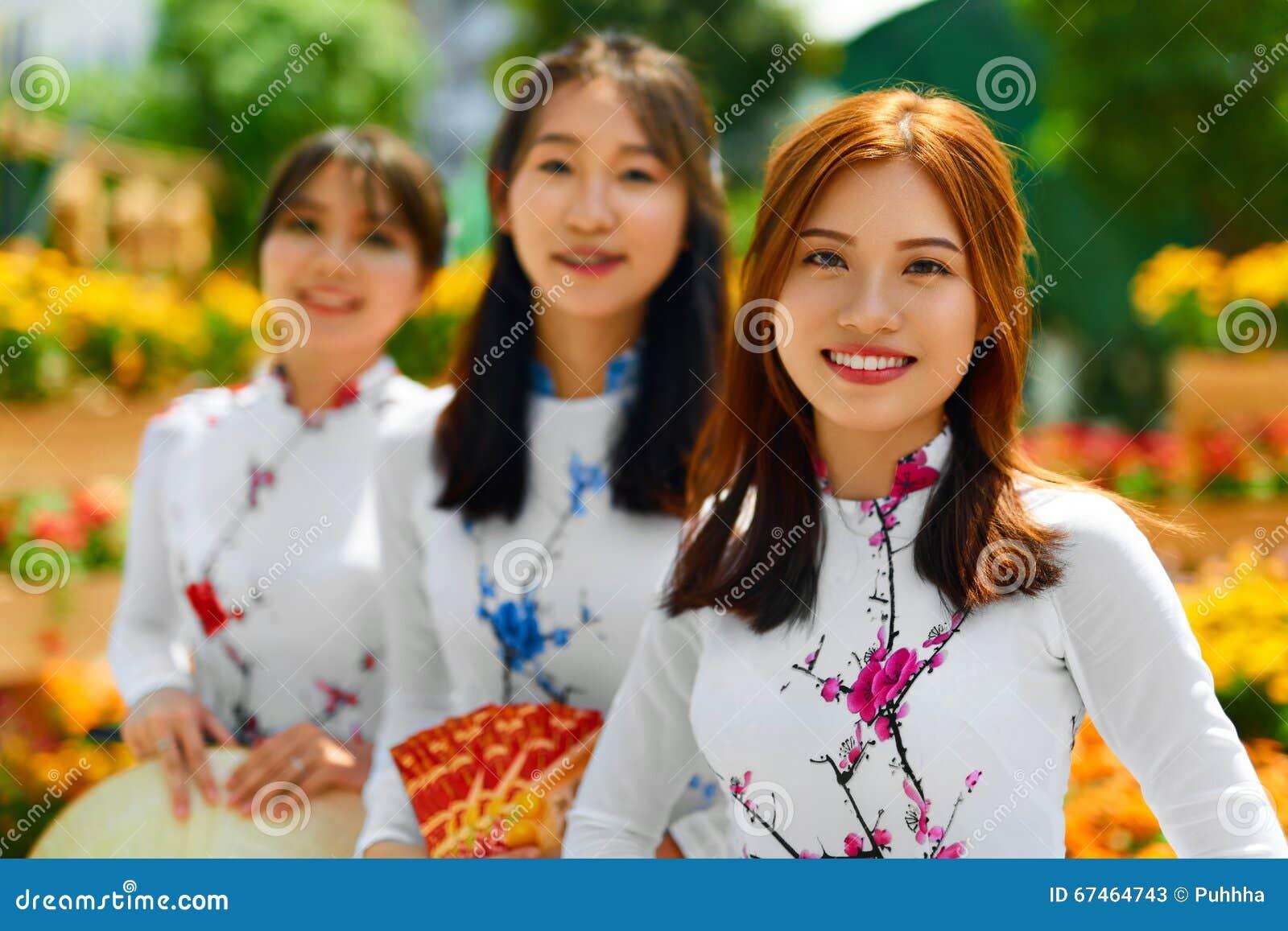 Povos asiáticos Mulheres felizes que vestem a roupa tradicional nacional