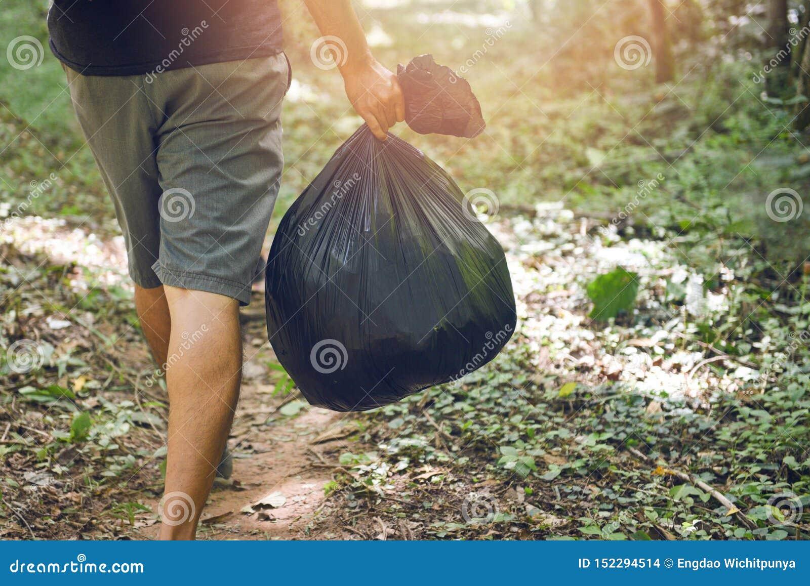 Povos da ecologia da recolha de lixo que limpam o parque - mão do homem que guarda sacos de lixo plásticos pretos na floresta, li