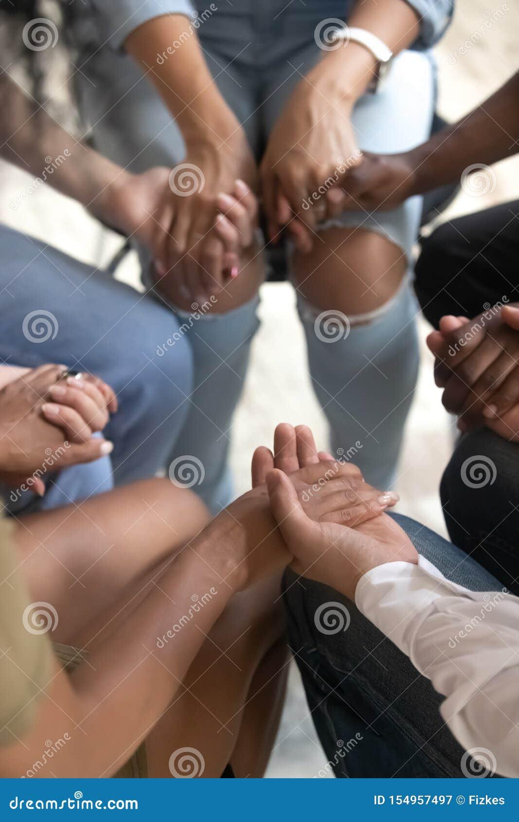 Povos da opinião do close up que sentam-se unidas mantendo as mãos durante a sessão de terapia