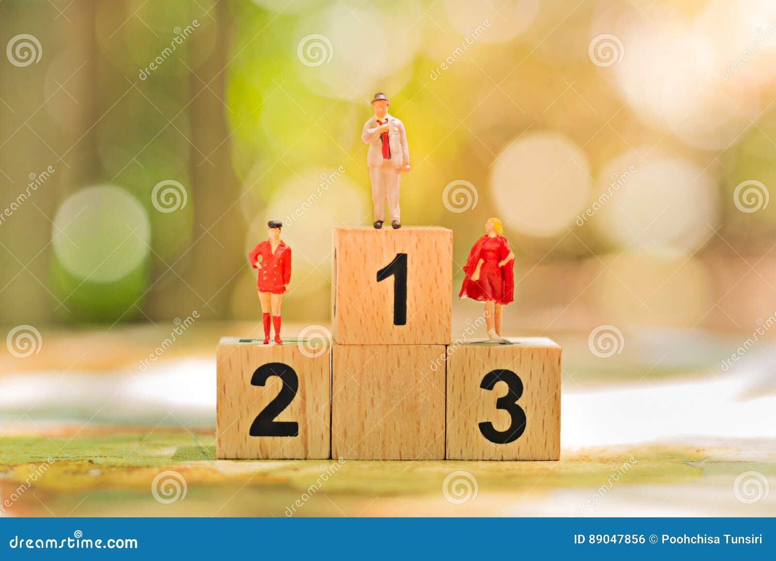 Povos diminutos: Figuras pequenas do trabalhador com posição de madeira do pódio Conceito da competição da equipe do negócio