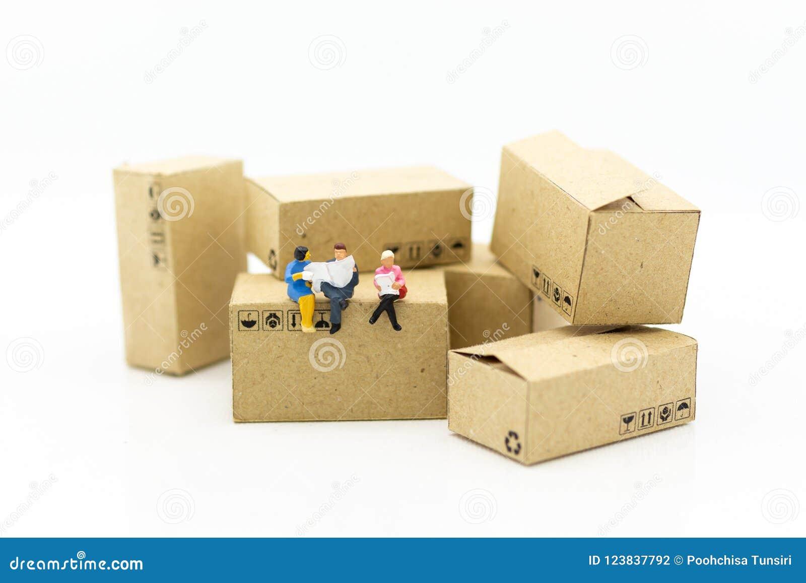 Povos diminutos: Homem de negócios que senta-se na caixa no armazém Uso da imagem para o conceito do negócio, o industrial e o lo