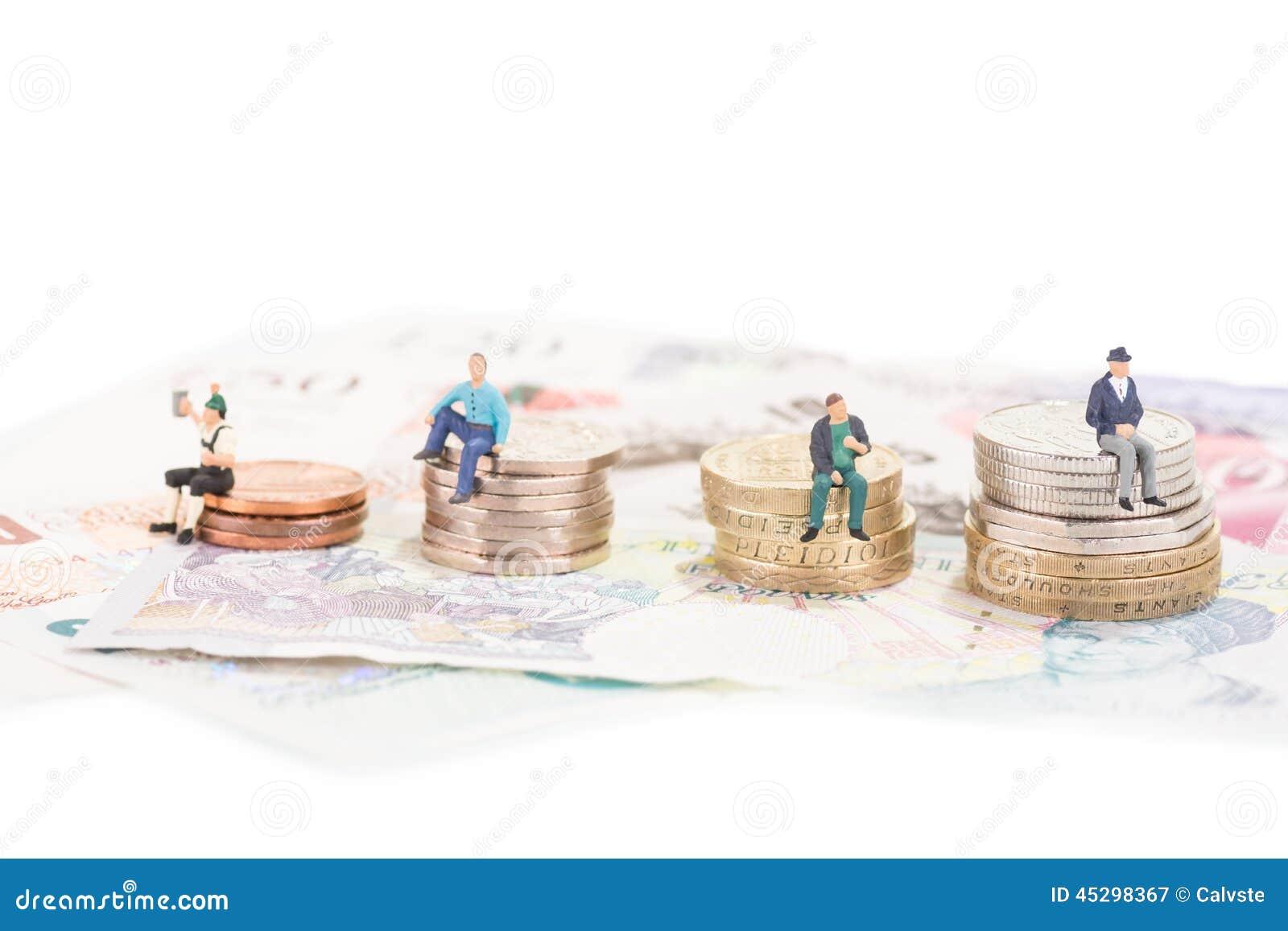 Povos diminutos que sentam-se no close-up das moedas