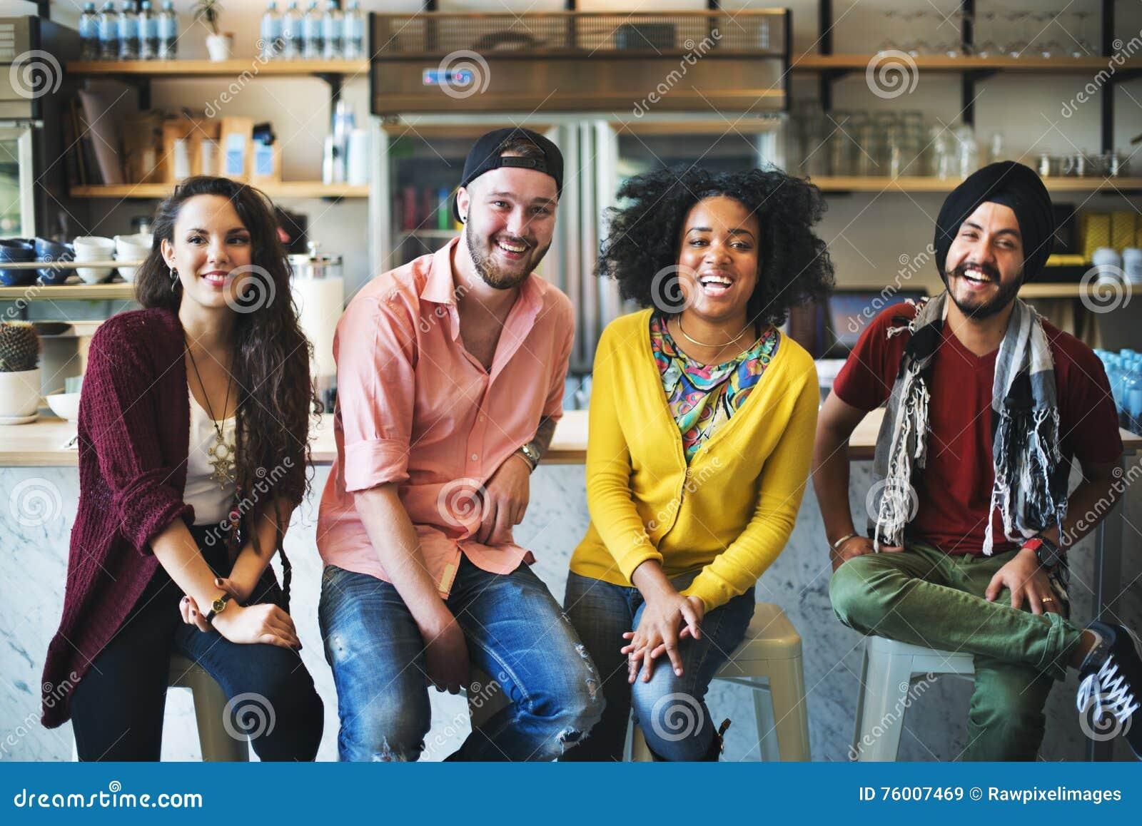 Povos diversos que sentam o conceito alegre da amizade