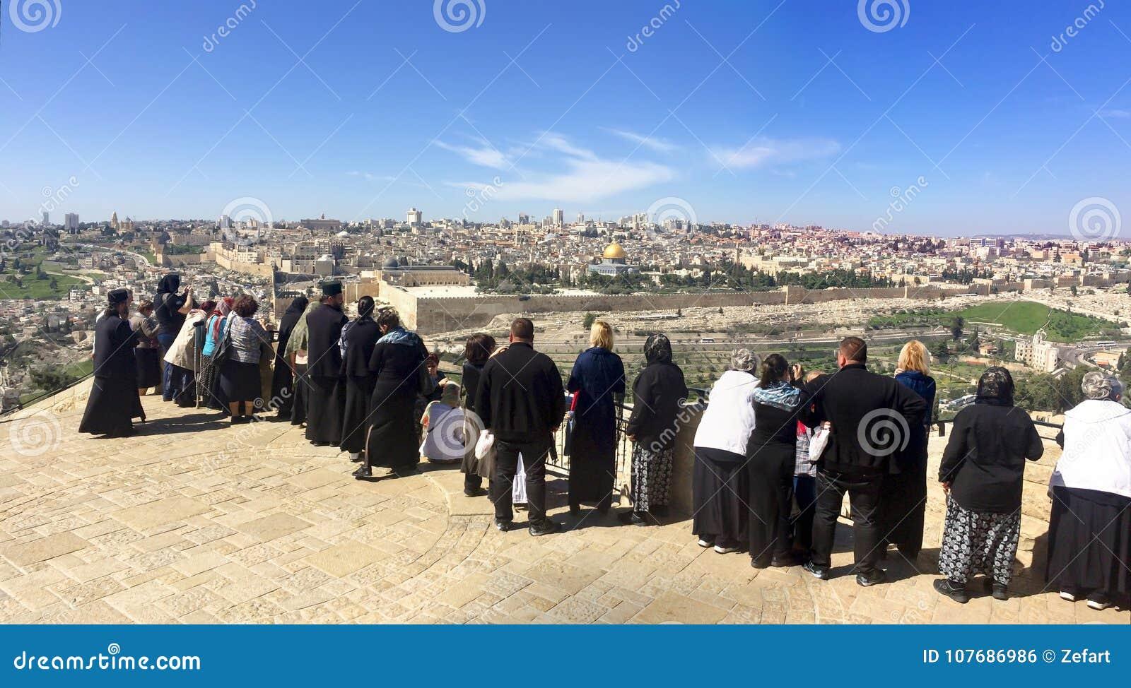 Povos do turista na vista panorâmica à cidade velha Temple Mount do Jerusalém e ao cemitério judaico antigo na montanha verde-oli