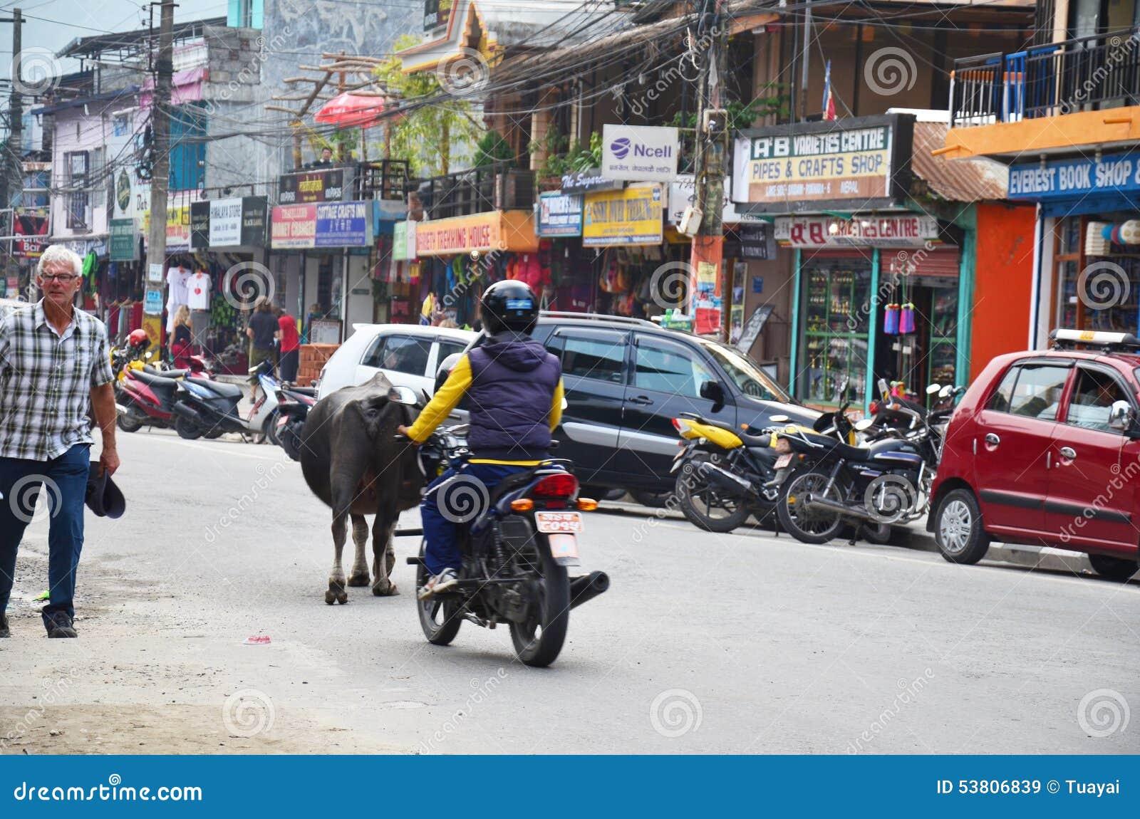 Povos e tráfego na estrada no mercado de rua de Pokhara
