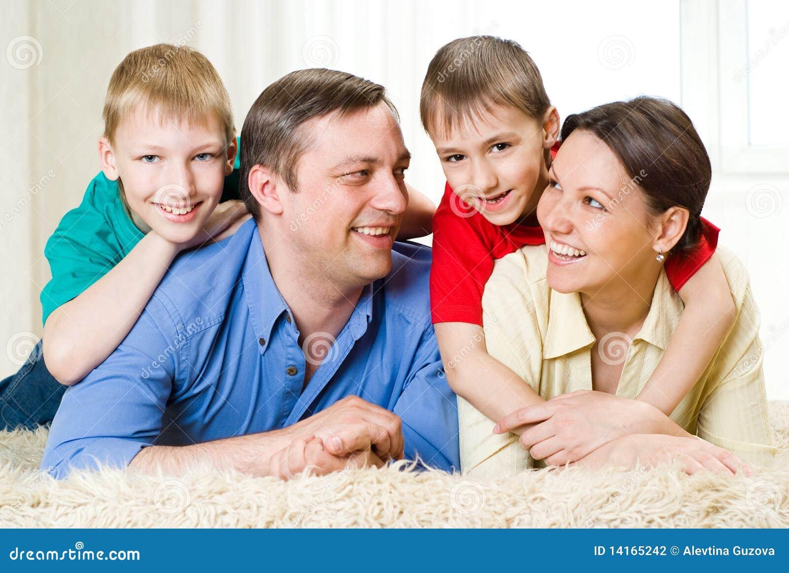 Povos felizes do agregado familiar com quatro membros