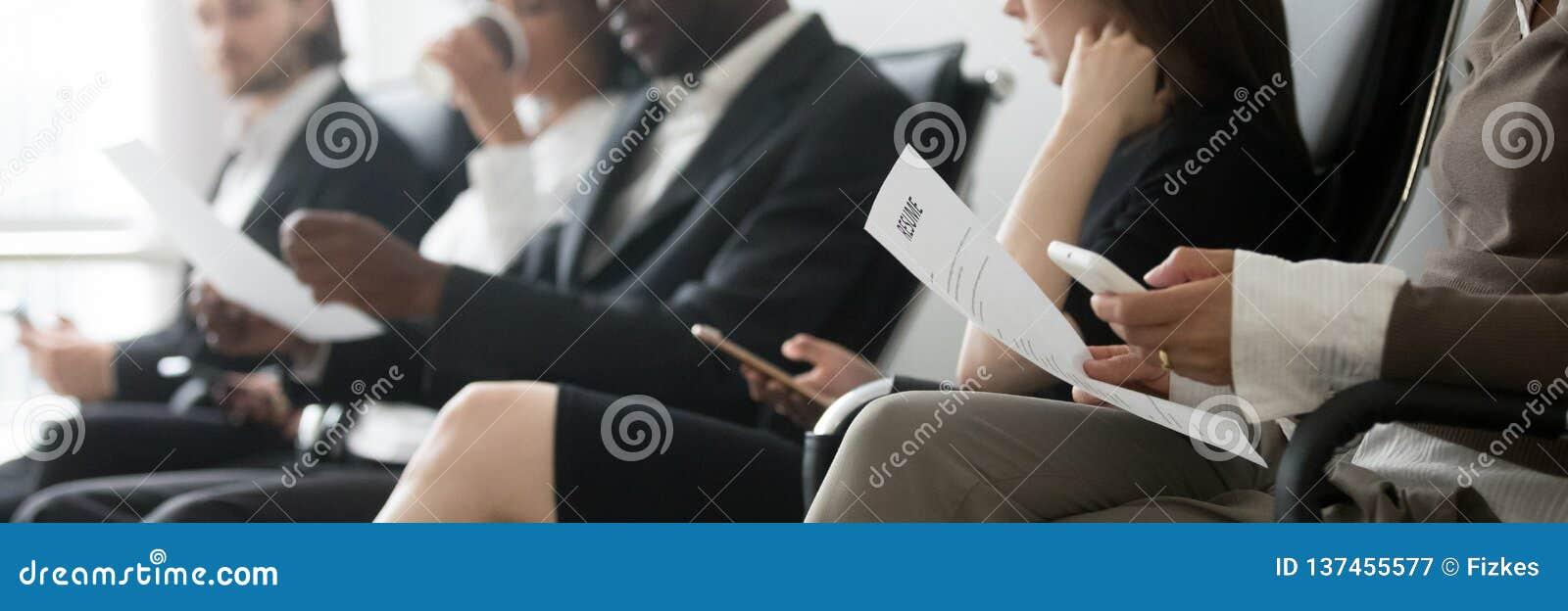 Povos multirraciais da foto horizontal lateral que sentam-se na entrevista de espera da fila