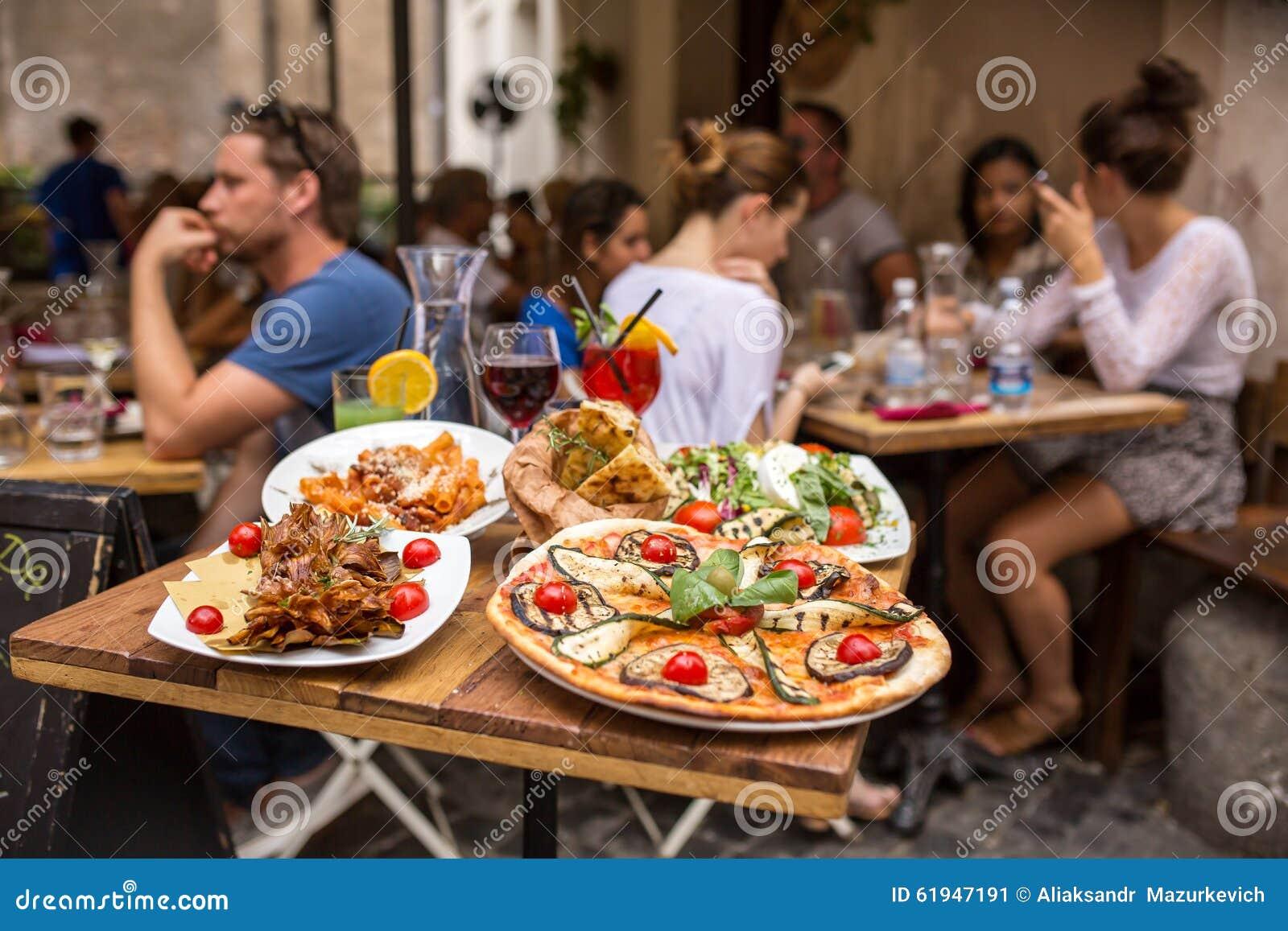Povos não identificados que comem o alimento italiano tradicional no restaurante exterior