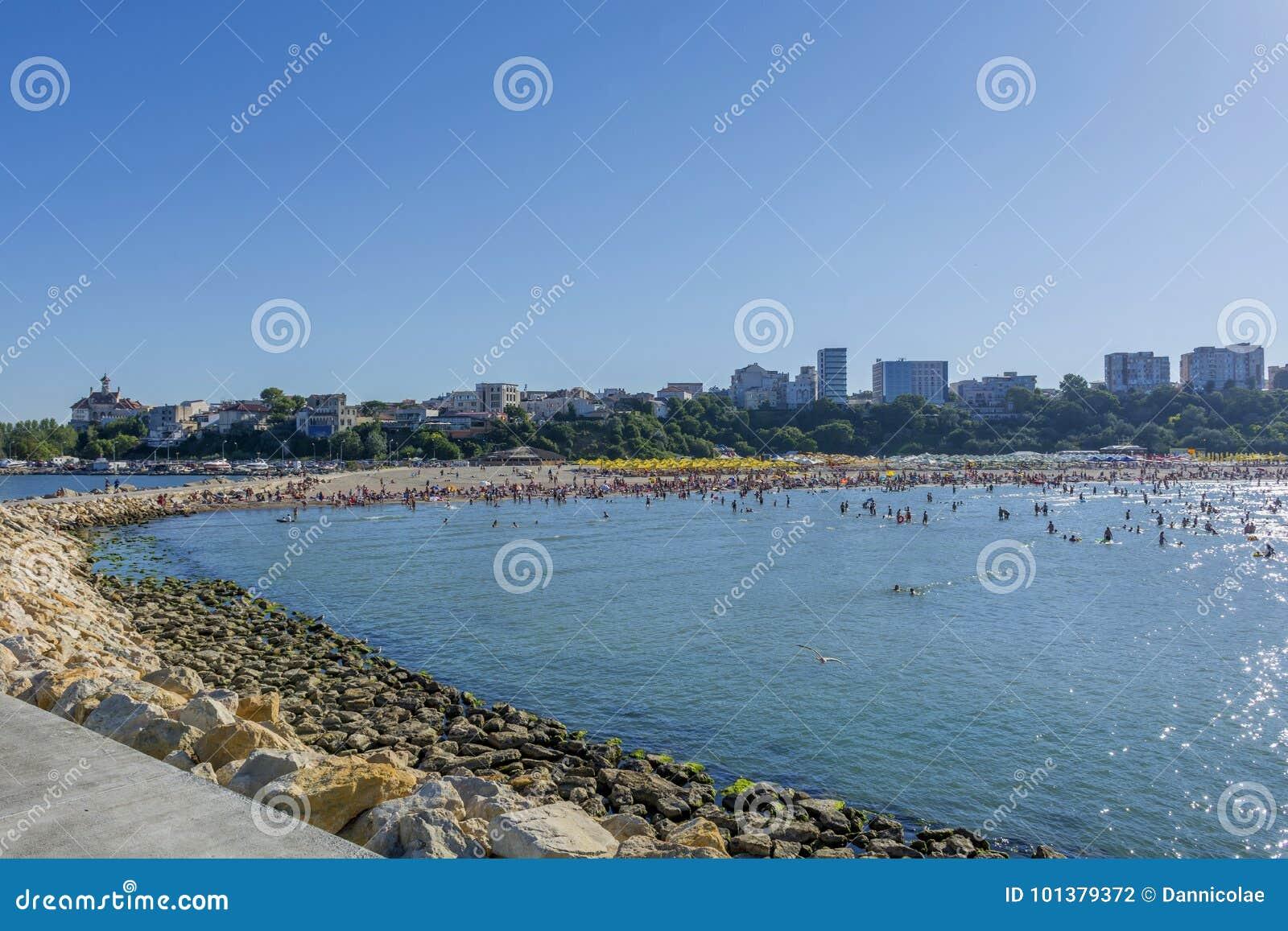 Povos na praia, no banho de sol e na natação, apreciando em férias