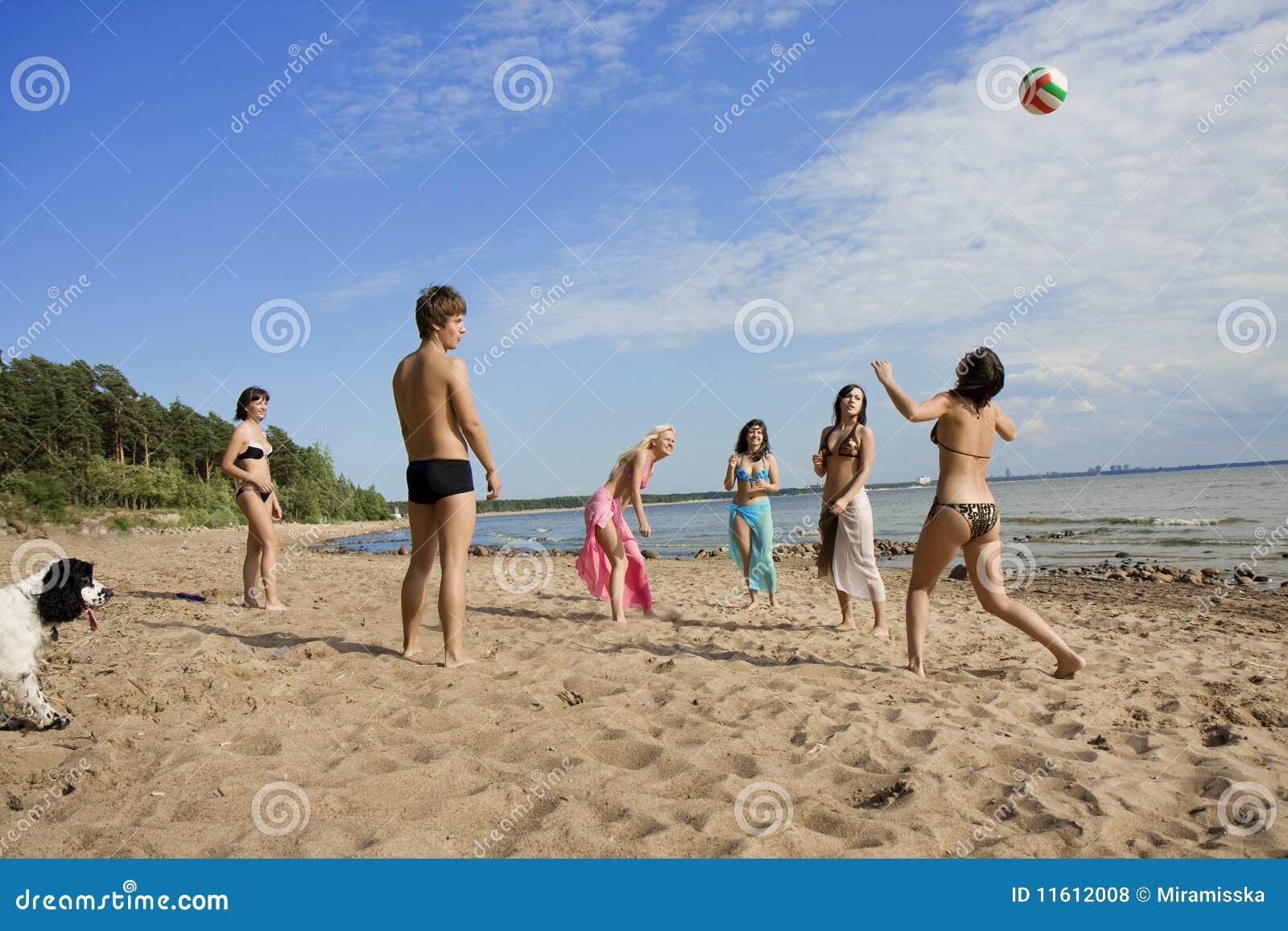Povos na praia que joga o voleibol
