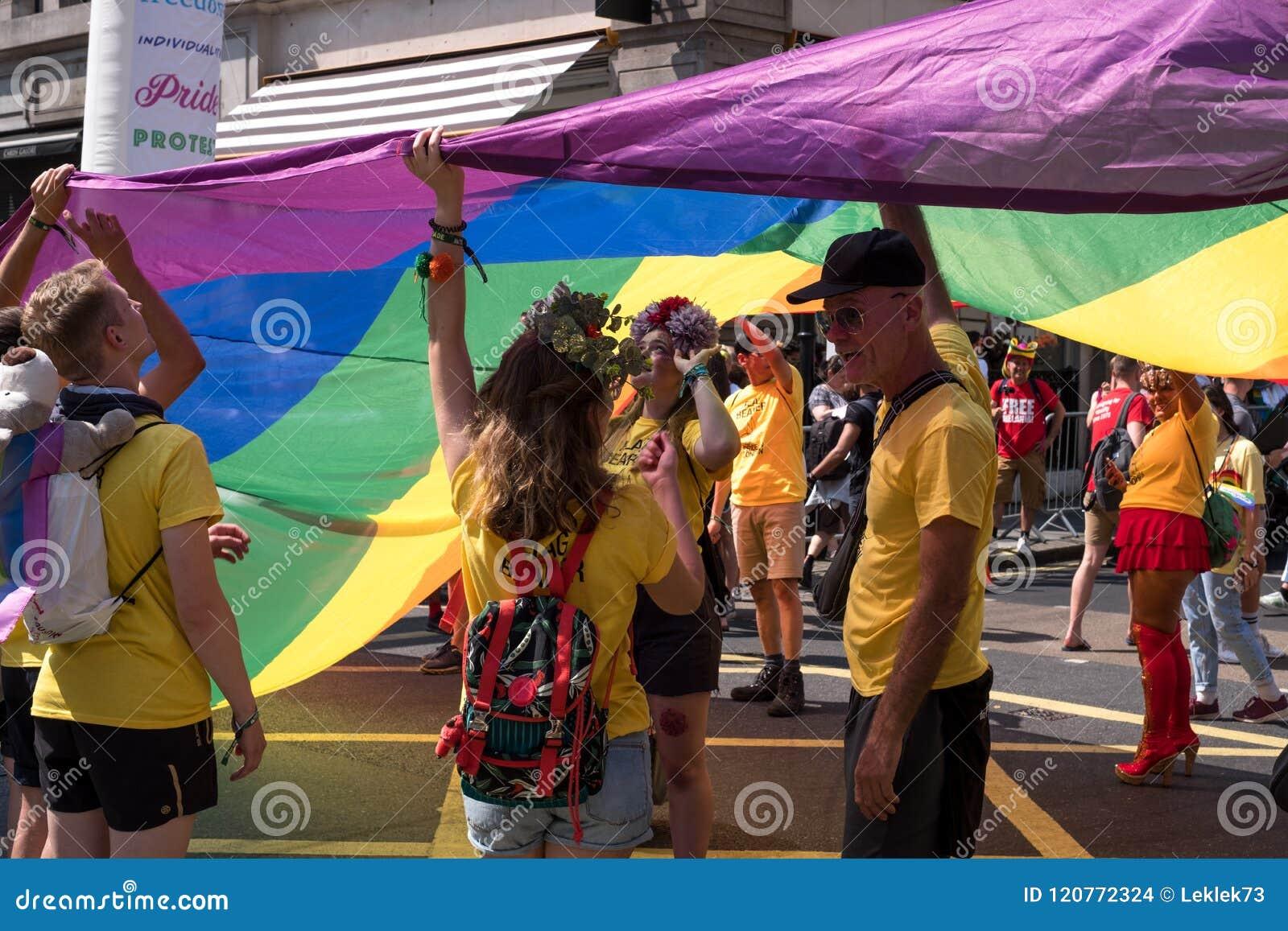 Povos nos t-shirt amarelos que estão sob a bandeira gigante do arco-íris de LGBT durante Pride Parade alegre 2018