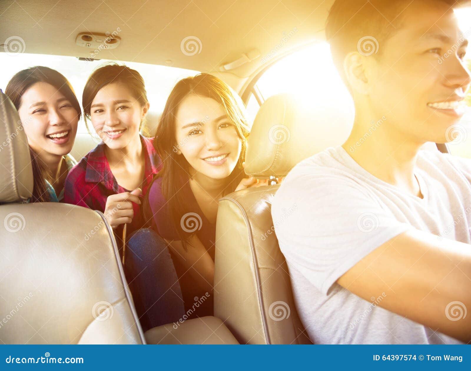 Povos novos do grupo que apreciam a viagem por estrada no carro