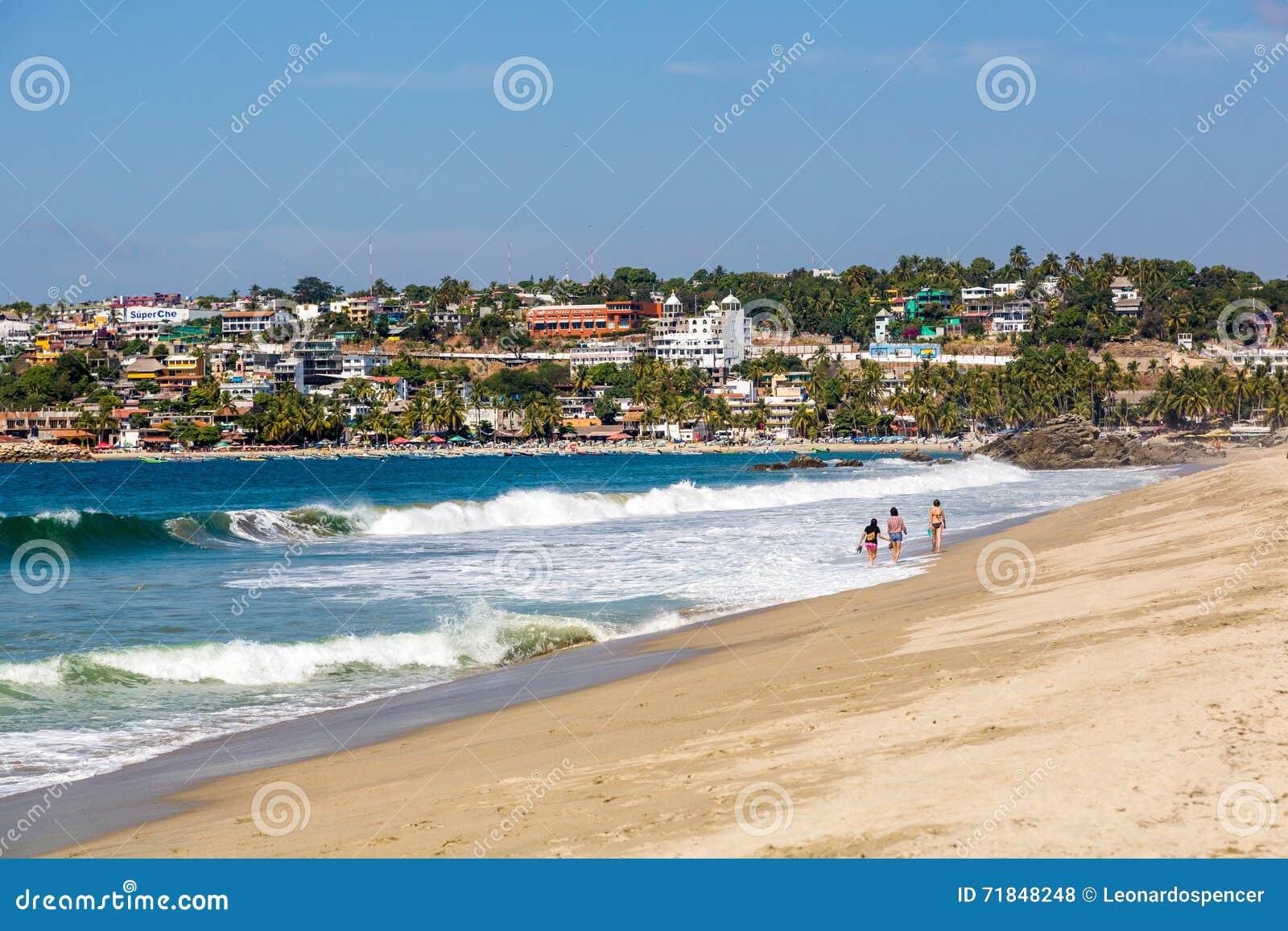 Povos que andam na praia de Puerto Escondido,