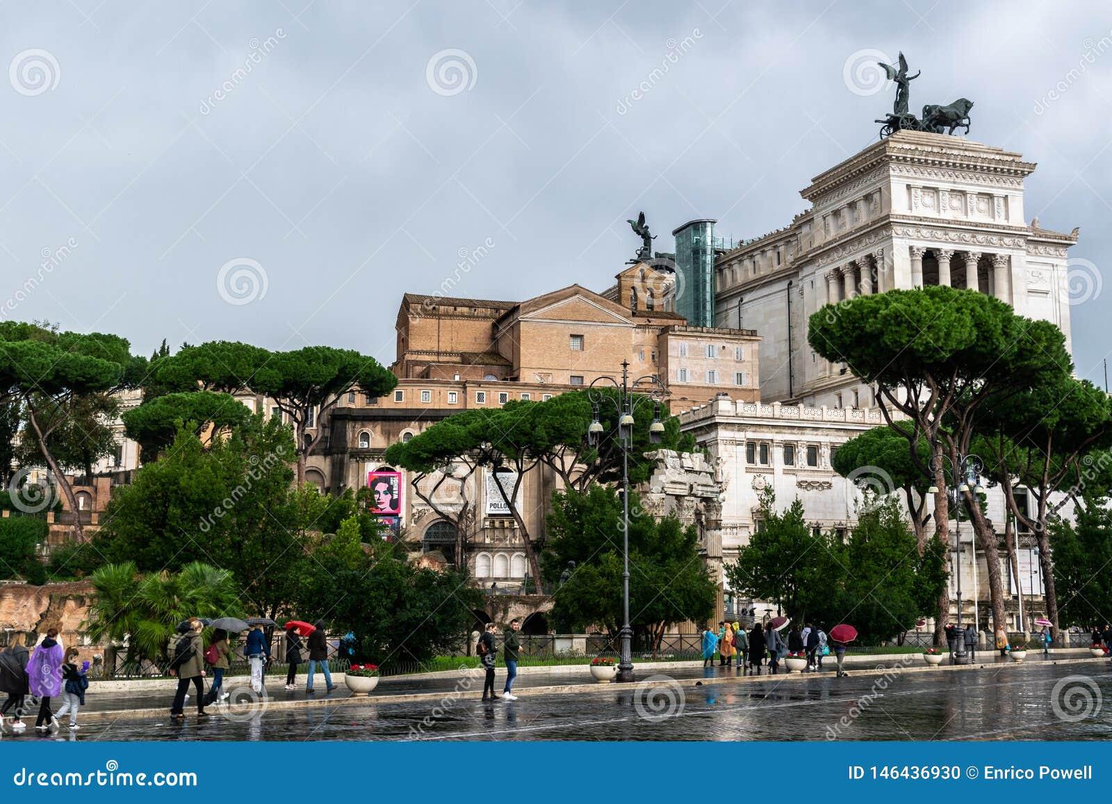 Povos que andam sobre através da rua de Dei Fori Imperiali O monumento de Vittorio Emanuele II altera-se da pátria no fundo