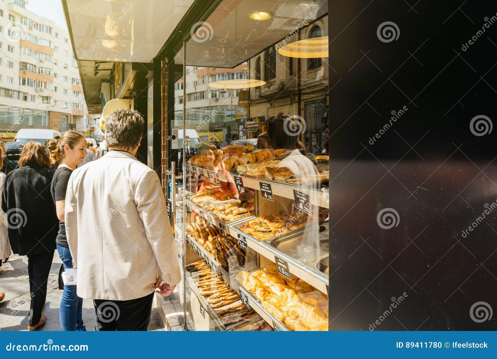 Povos que compram o alimento romeno tradicional em Bucareste no stre