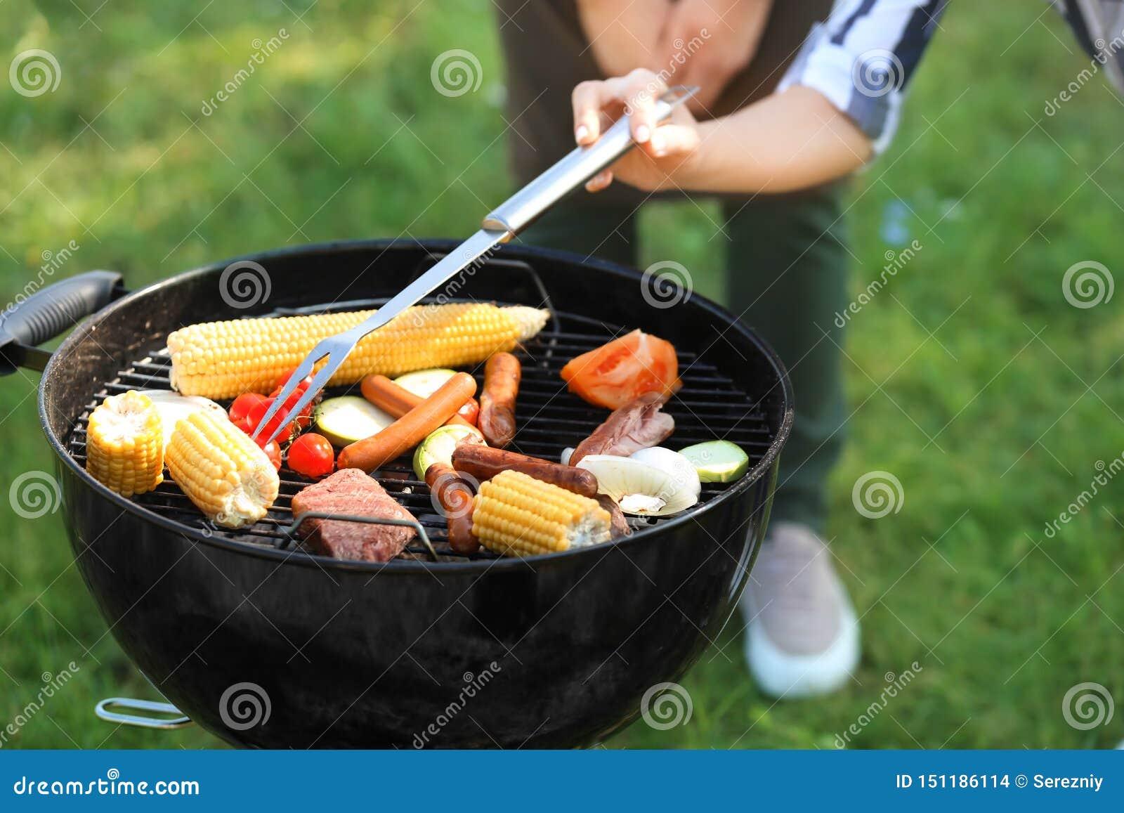 Povos que cozinham o alimento saboroso no ar livre da grade do assado, close up