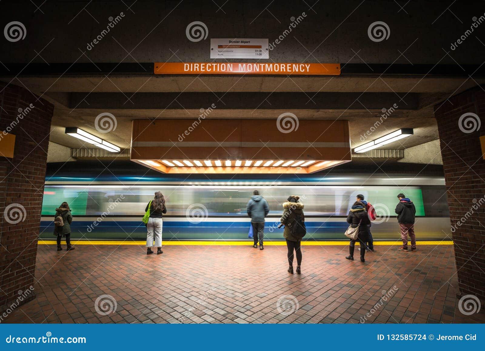 Povos que esperam um metro na plataforma da estação de Snowdon, linha alaranjada, quando um trem do metro vier, com um borrão da