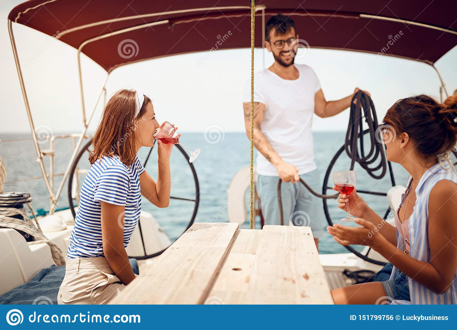 Povos que sentam-se na plataforma do veleiro e que têm o divertimento F?rias, curso, mar, amizade e conceito dos povos