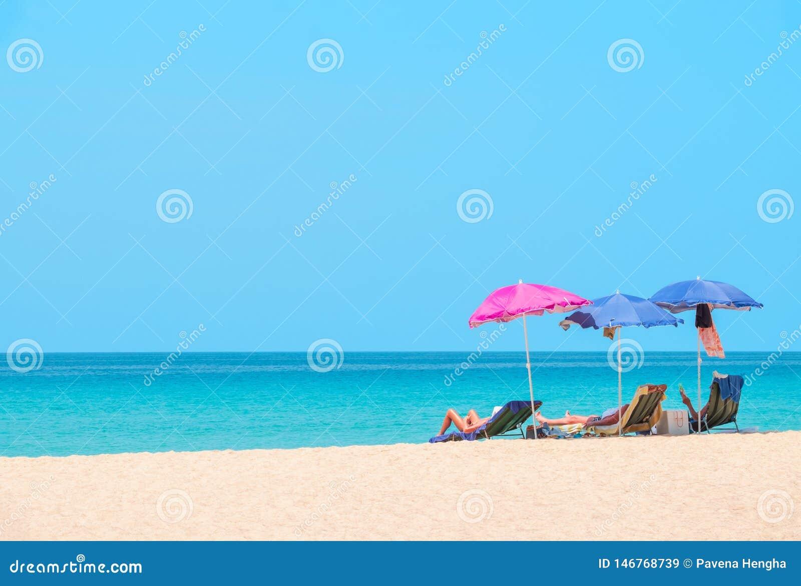 Povos que tomam sol e que relaxam em cadeiras de praia