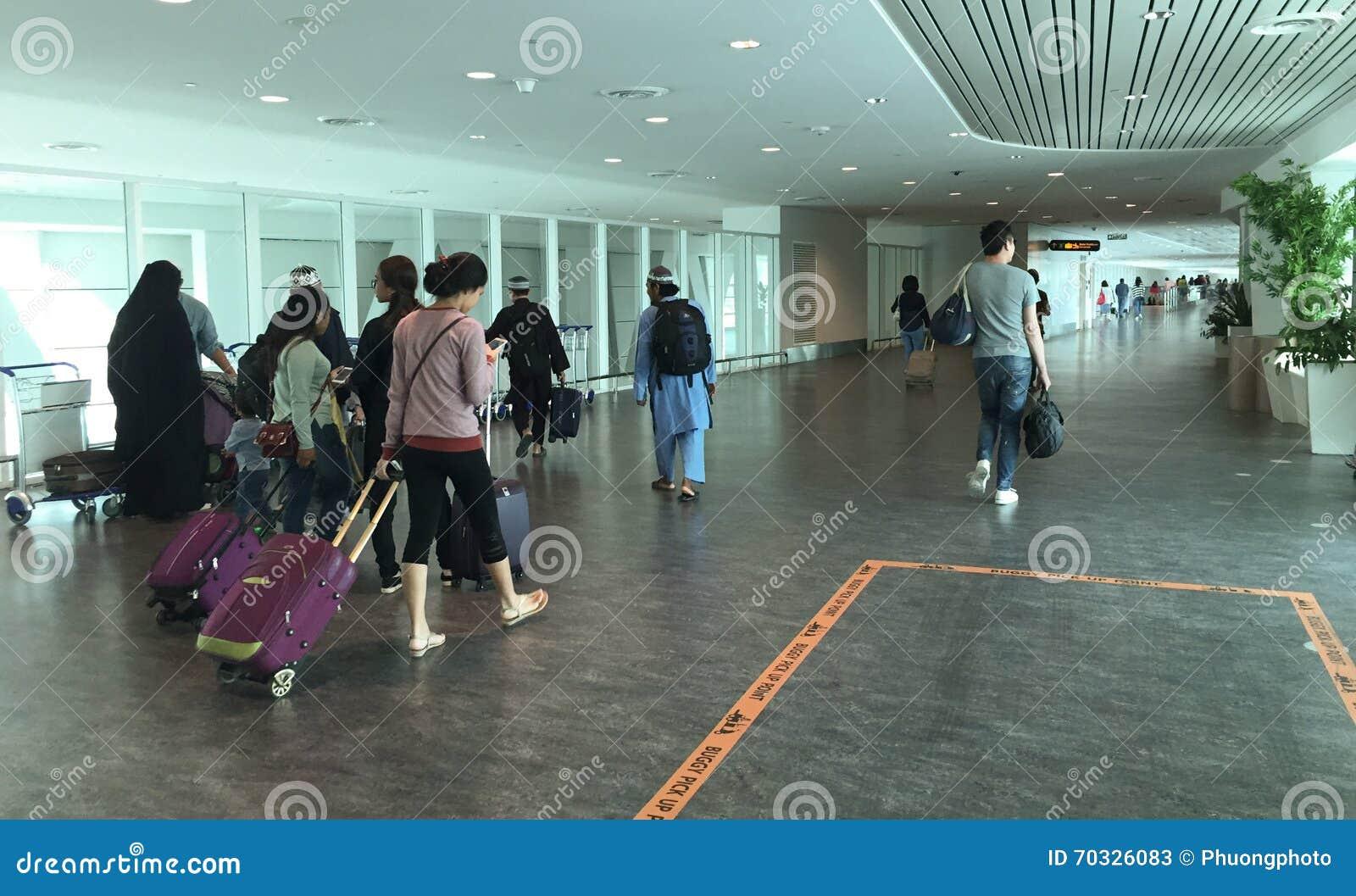 Povos que vão às portas de embarque em Tan Son Nhat Airport, Saigon, Vietname