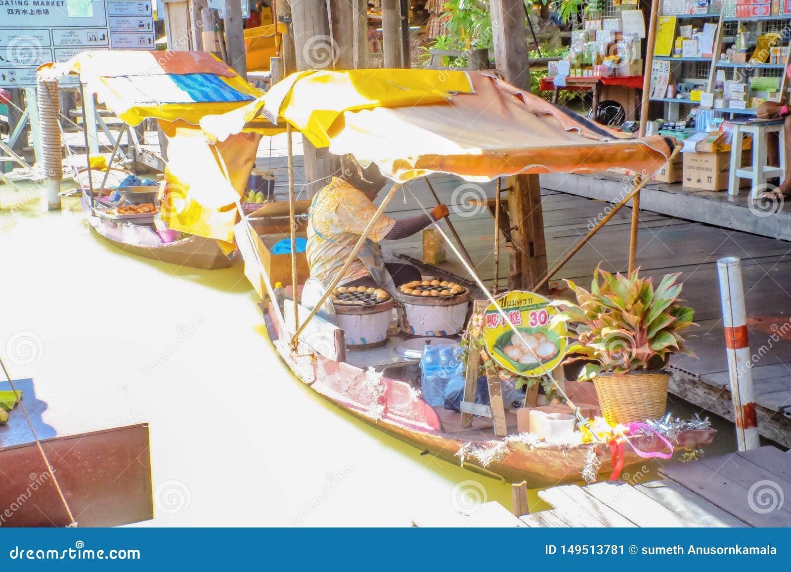 Povos tailandeses Unacquainted que vendem o bolo de coco famoso tailandês do alimento da rua no barco no mercado de flutuação do