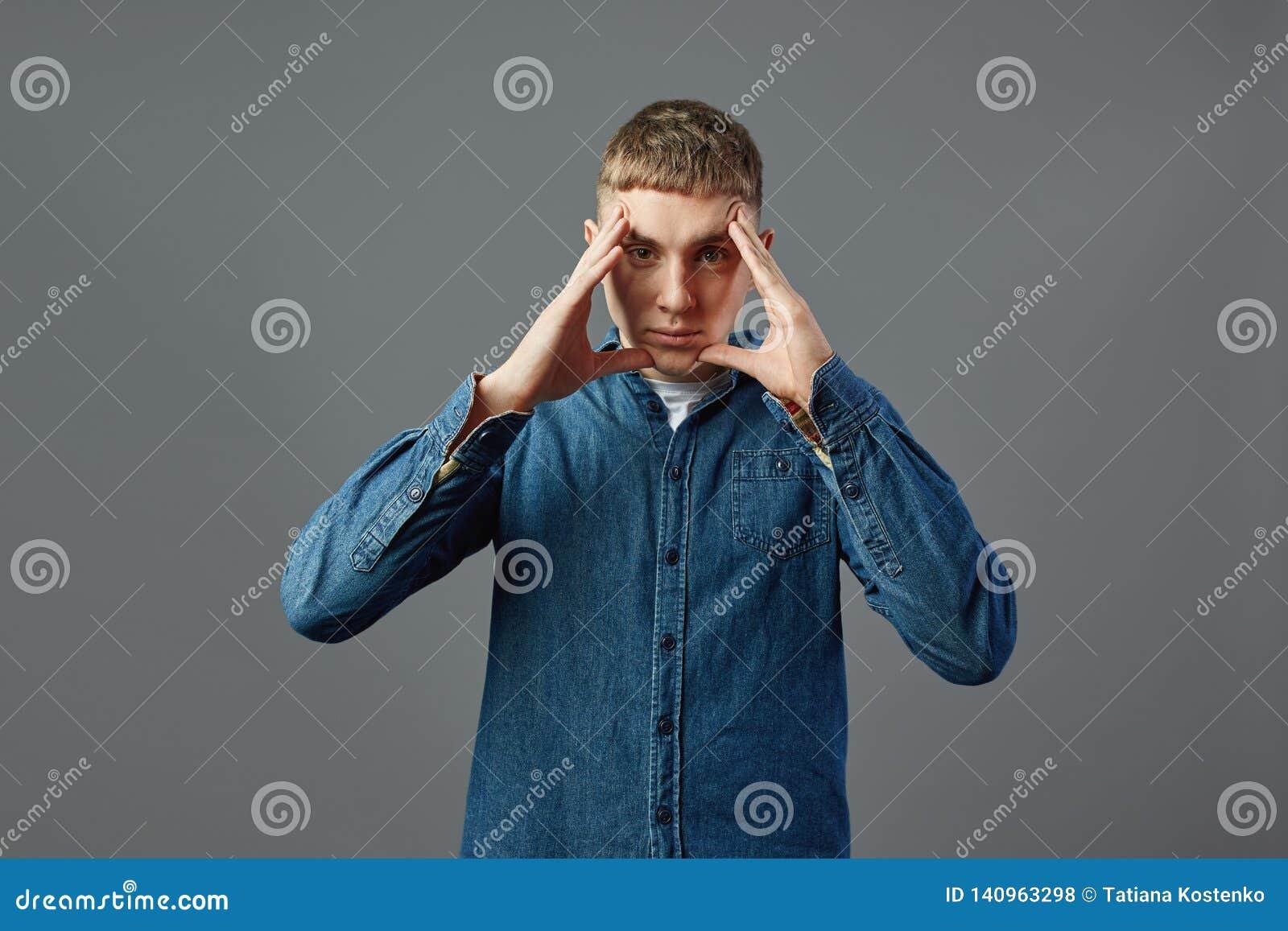 Poważny facet ubierał w cajg koszulowej pozycji z jego rękami na jego twarzy w studiu na szarym tle