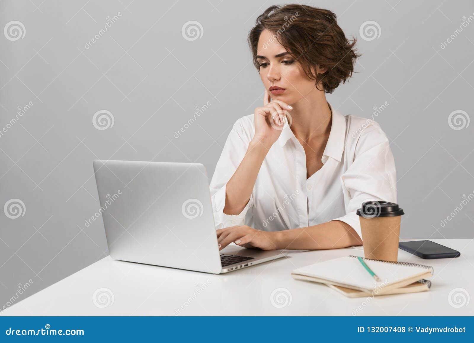 Poważna biznesowa kobieta pozuje nad popielatym ściennym tła obsiadaniem przy stołowym używa laptopem