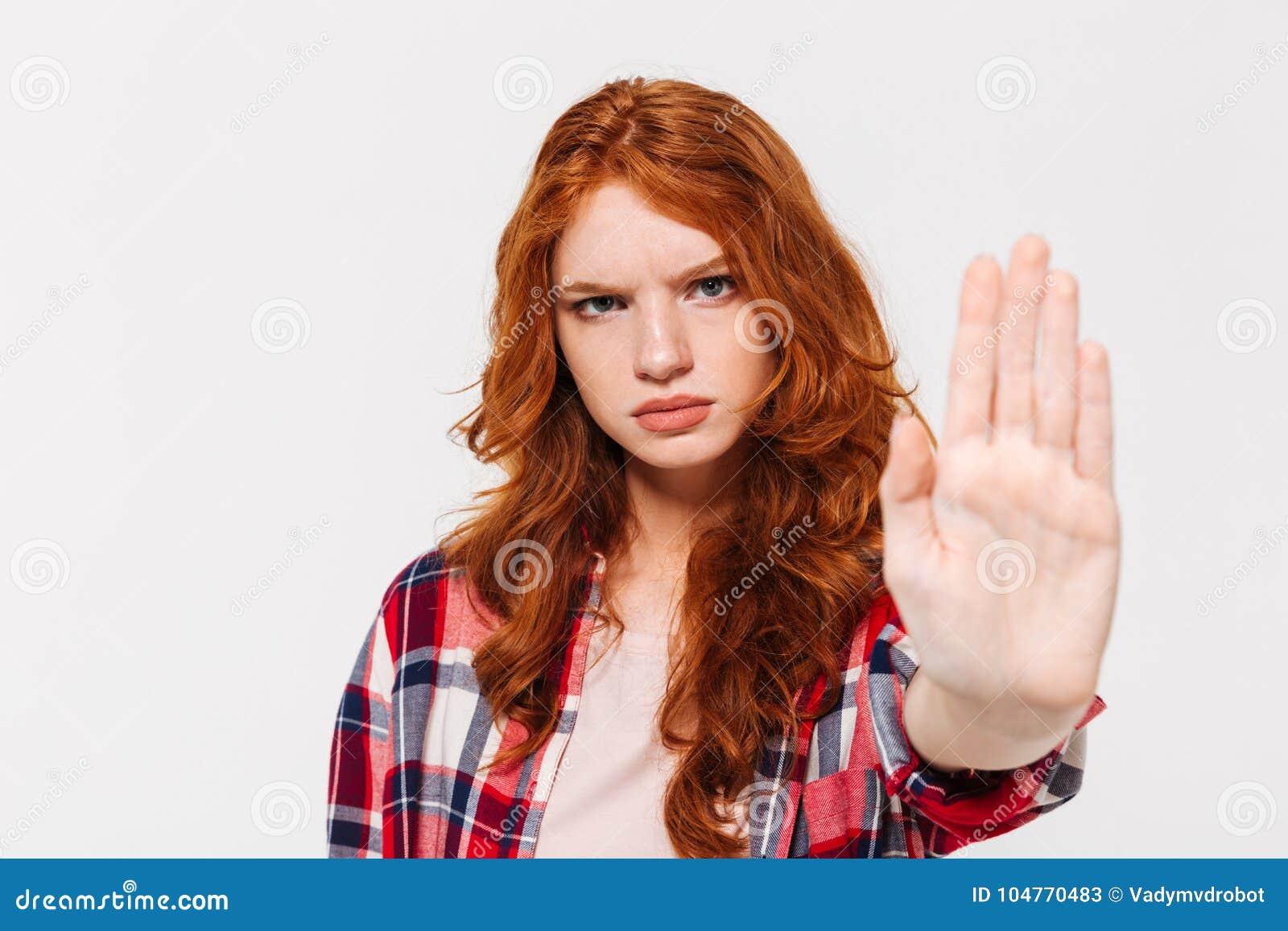 Poważna imbirowa kobieta w koszulowym seans przerwy gescie przy kamerą