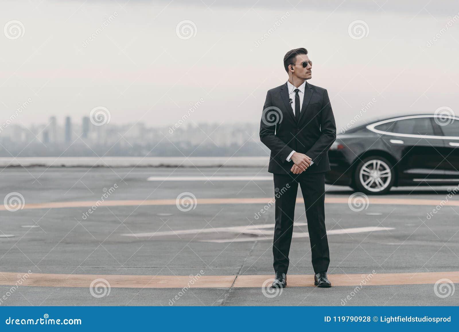 Poważna ochroniarz pozycja z okularami przeciwsłonecznymi i ochrony earpiece na lądowisku i patrzeć