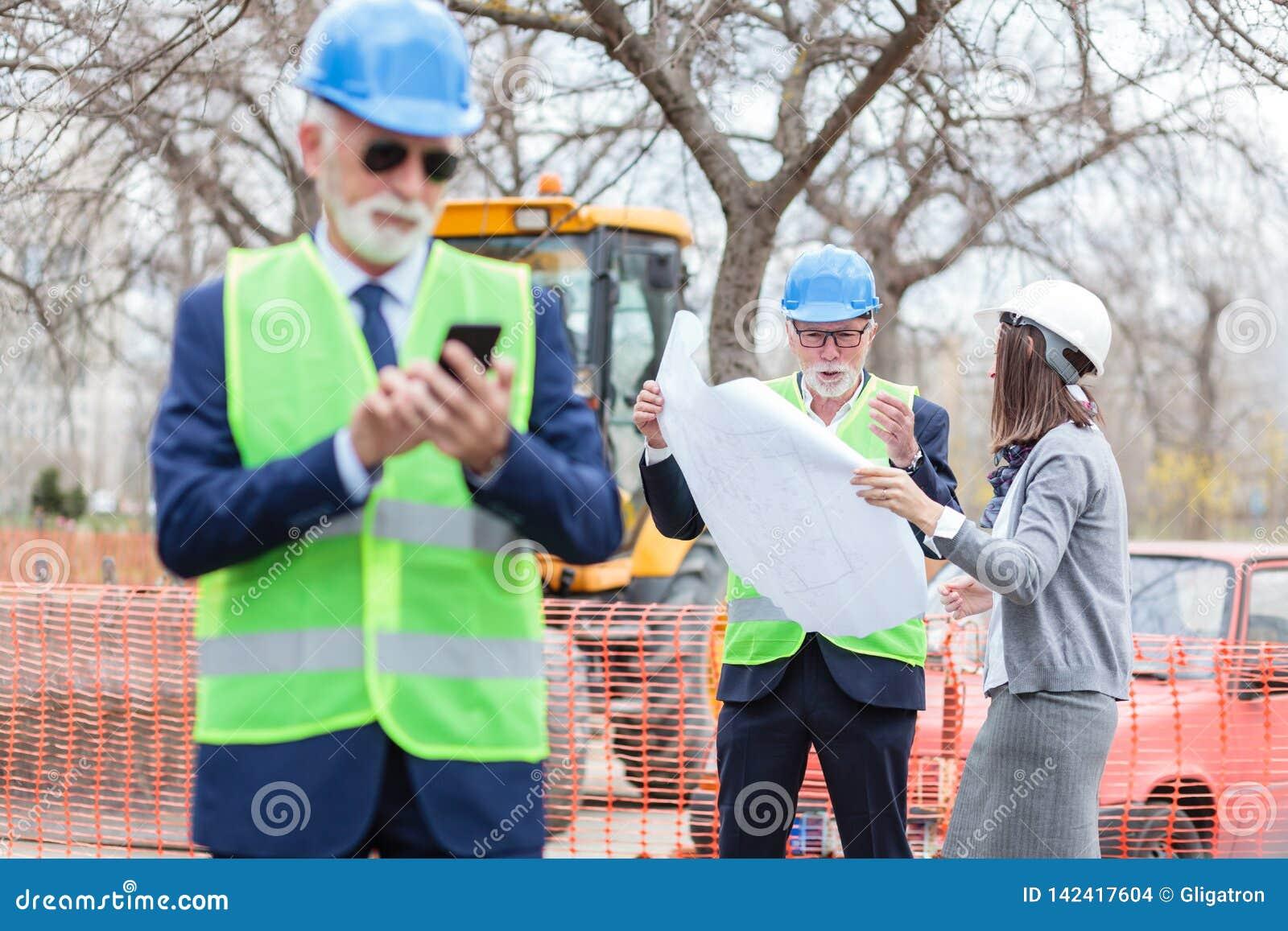 Poważna starsza samiec i potomstwo żeńscy architekci patrzeje budynków projekty partnery biznesowi lub