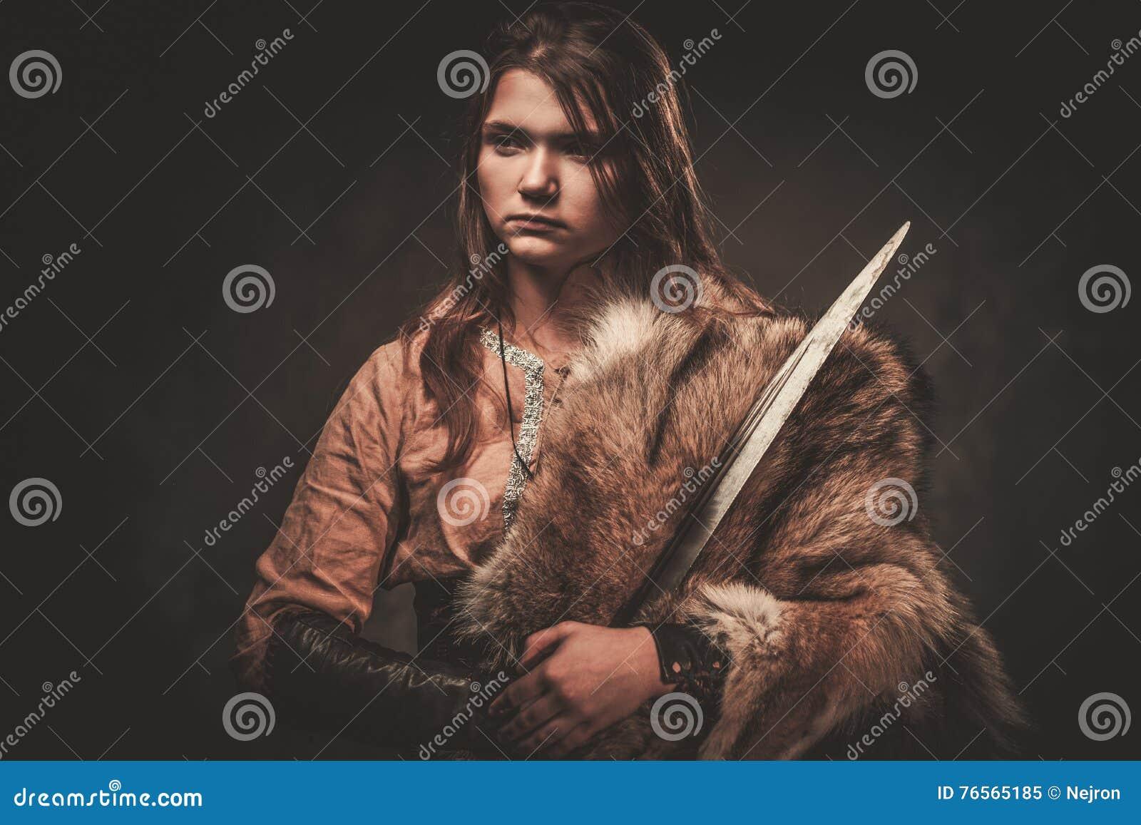 Poważna Viking kobieta z kordzikiem w wojownika tradycyjnych ubraniach, pozuje na ciemnym tle