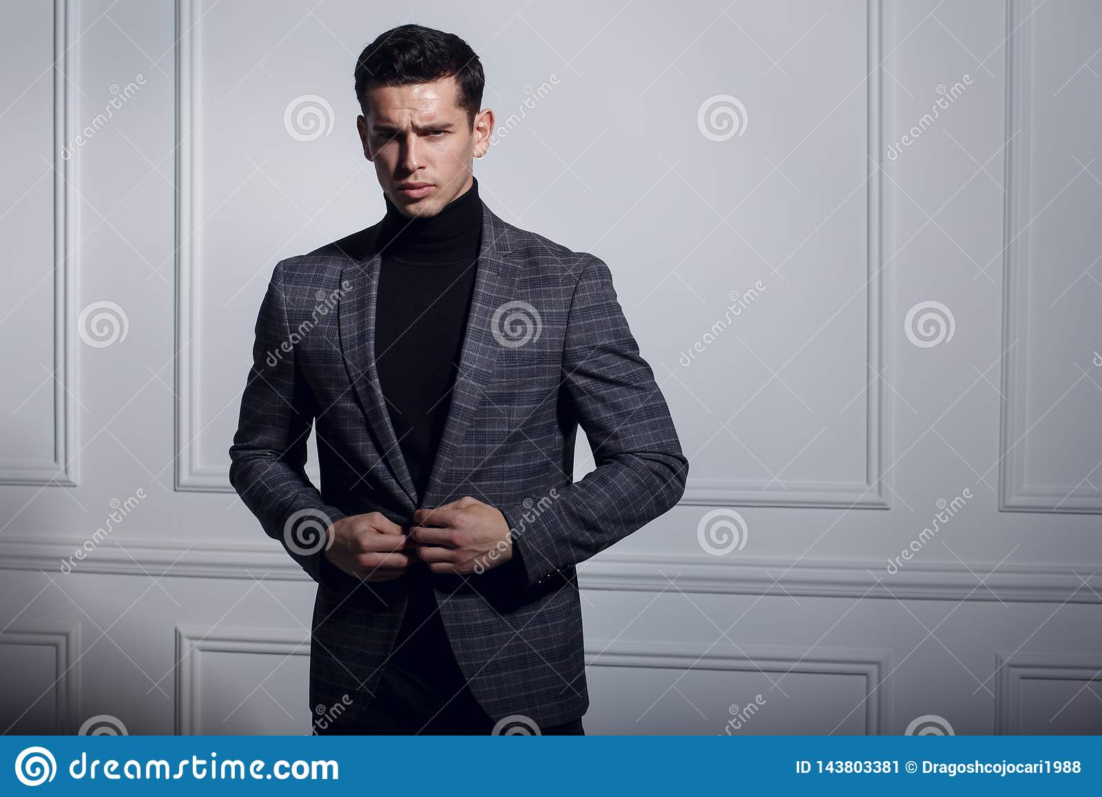 Poważnie nadaje się portret mężczyzna w szarość, pozujący elegancką pobliską biel ścianę w studiu, na białym tle