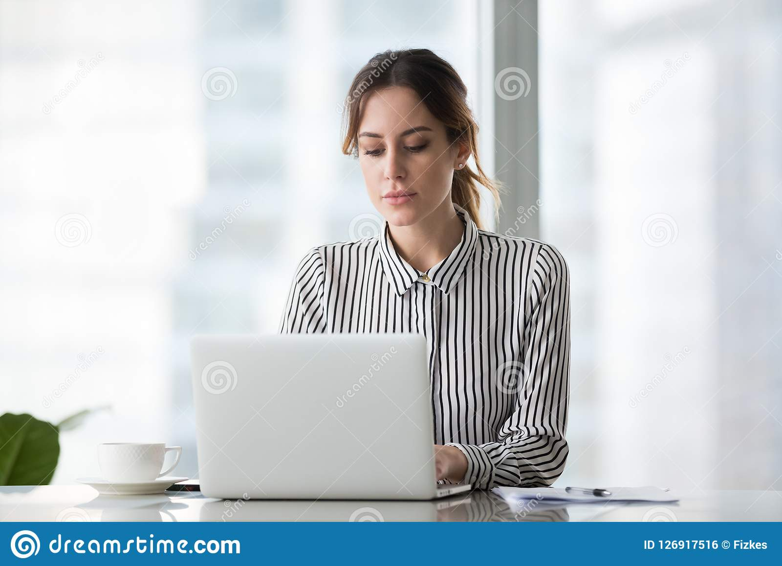 Poważny bizneswoman pracuje online używać laptop przy biurem
