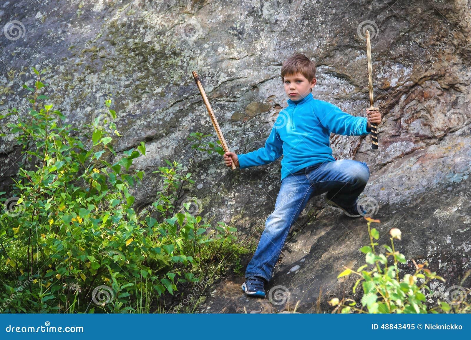 Poważny dzieciak z drewnianym kordzikiem na kamieniu