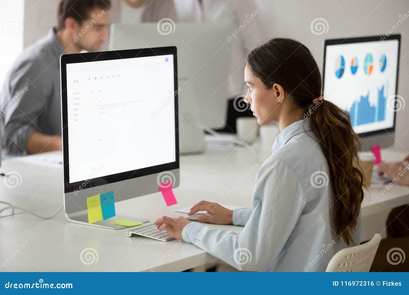 Poważny dziewczyna stażysta skupiał się na writing emailu pracuje na komputerze